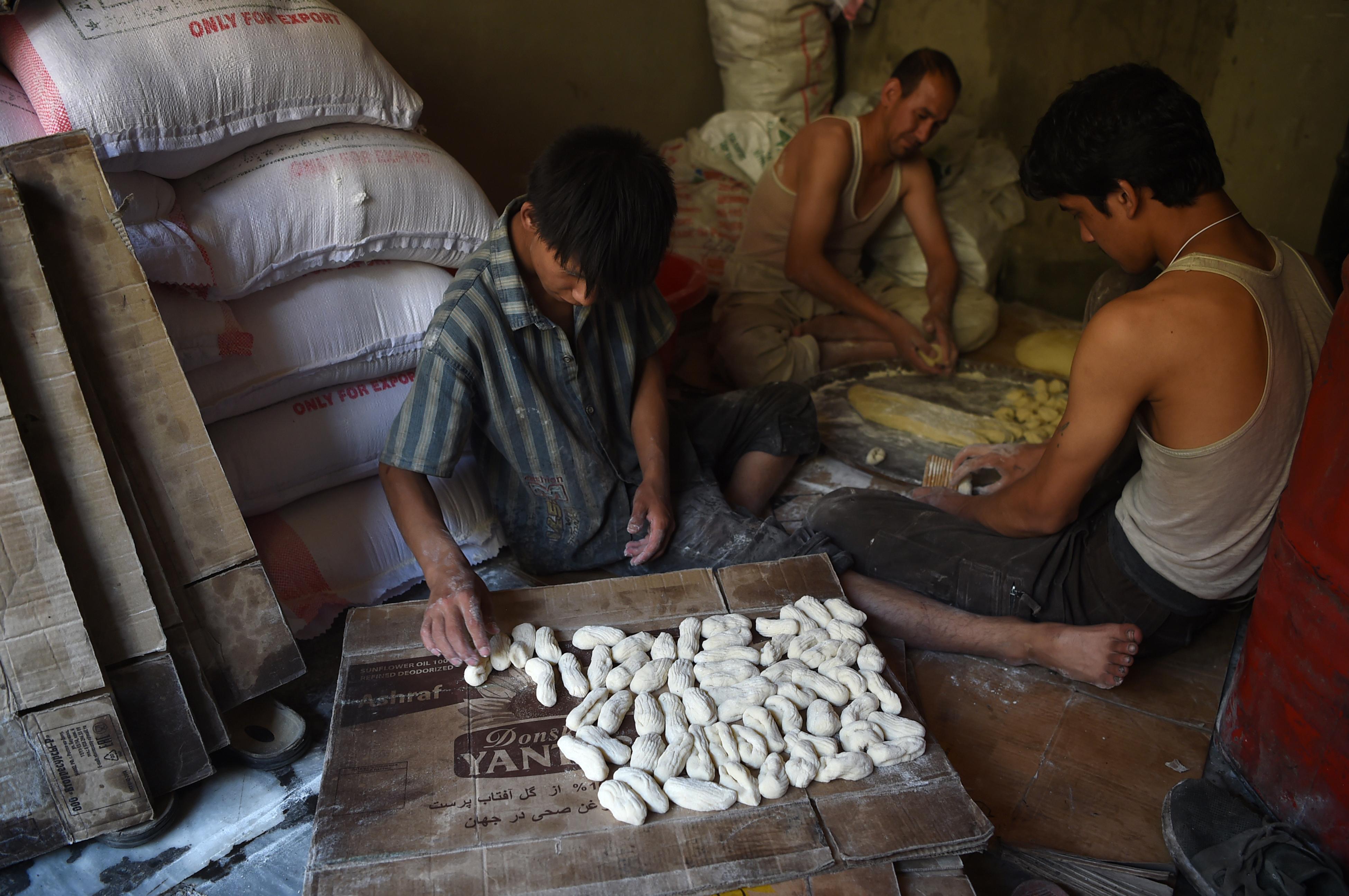عمال أفغان يقومون بتحضير حلوى خاجور التقليدية تحضيرا للعيد في كابول