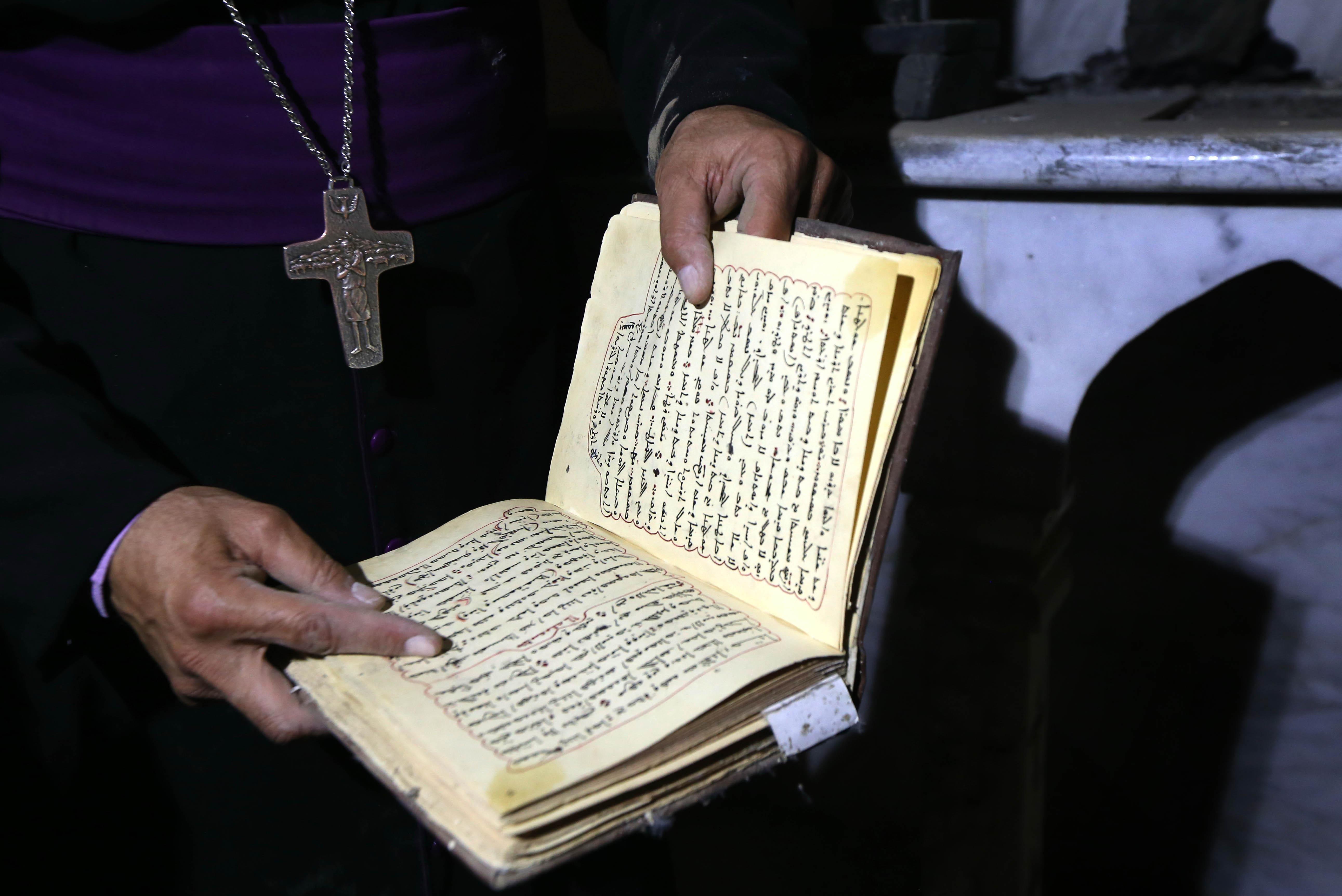 رجل دين مسيحي يحمل بين يده الإنجيل بعد عودته إلى برطلة