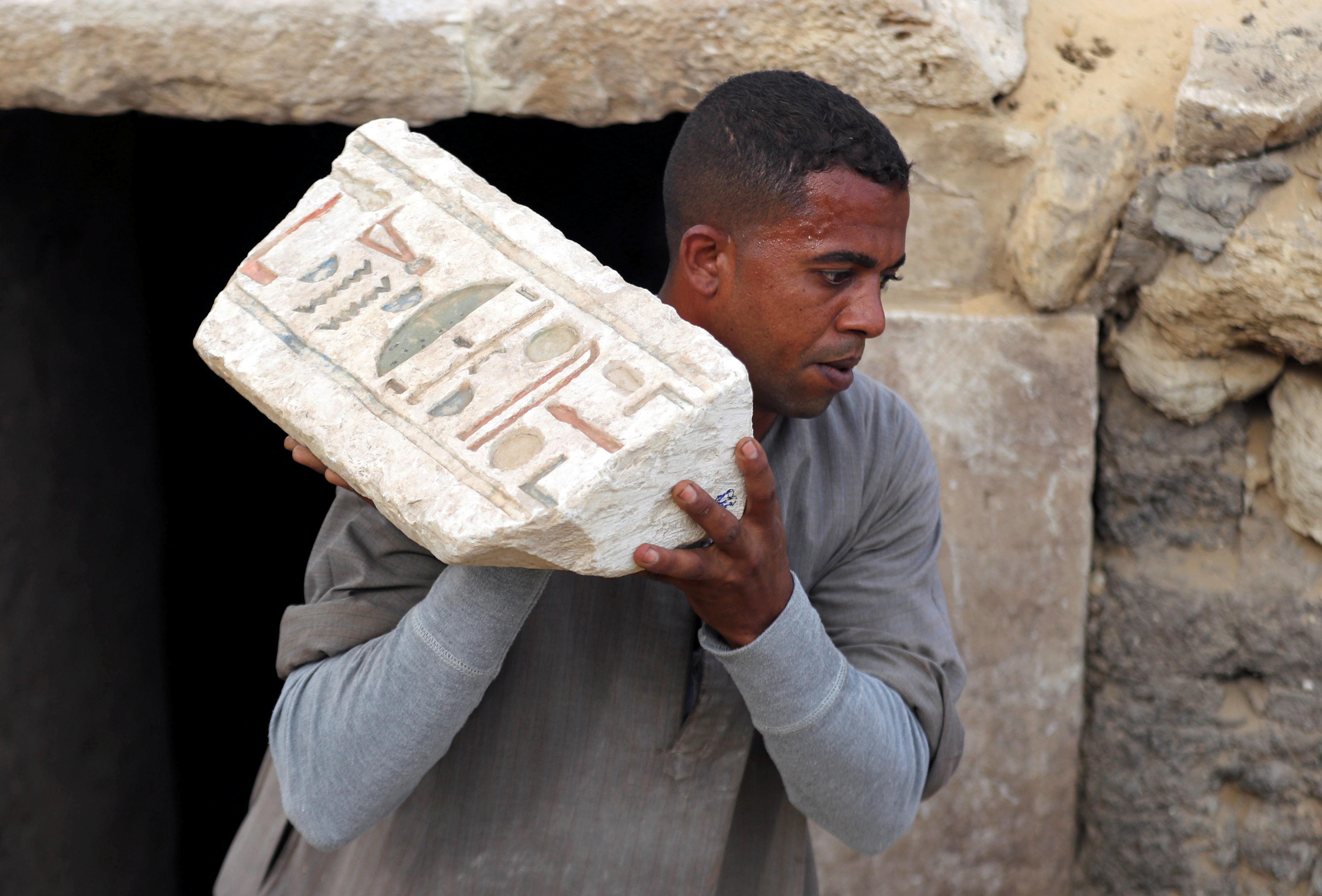 عامل يحمل قطعة آثرية في الاكتشاف الأثري الجديد في منطقة سقارة