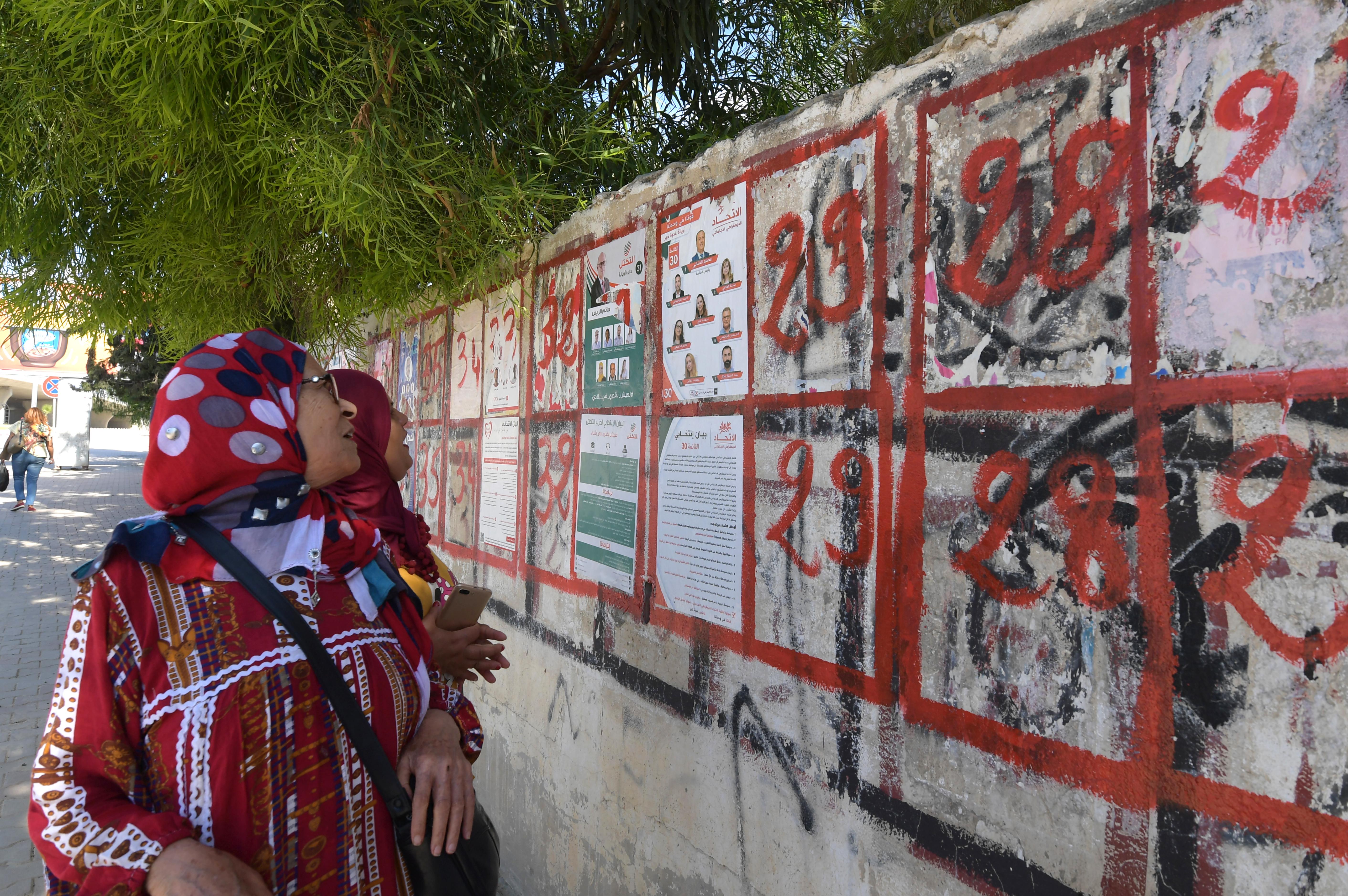 تونسيات تنظرن إلى دعايات ووعود انتخابية على جدار