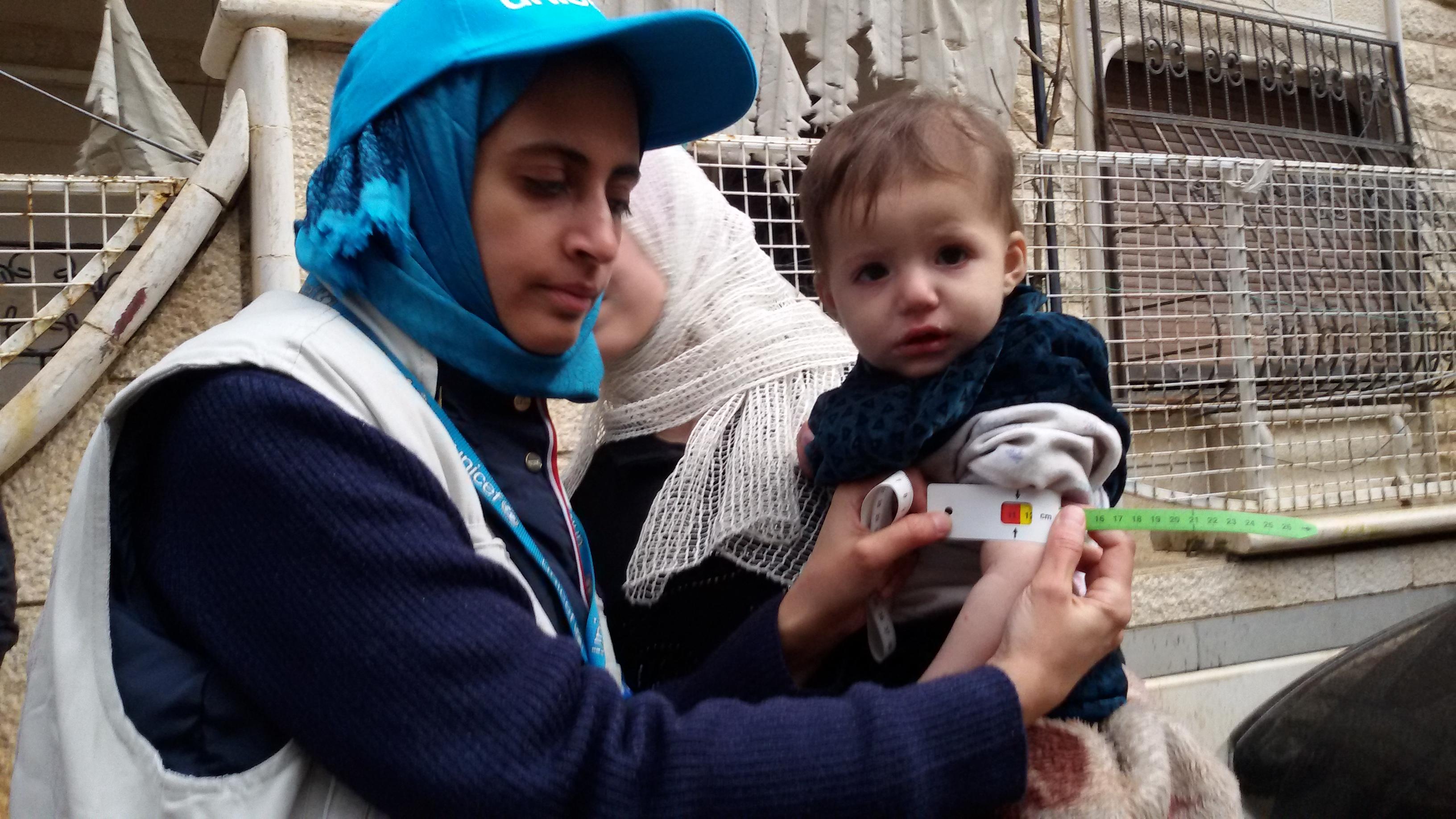 مسعفة باليونيسف تقيس ذراع طفل يعاني من سوء التغذية بمدينة مضايا