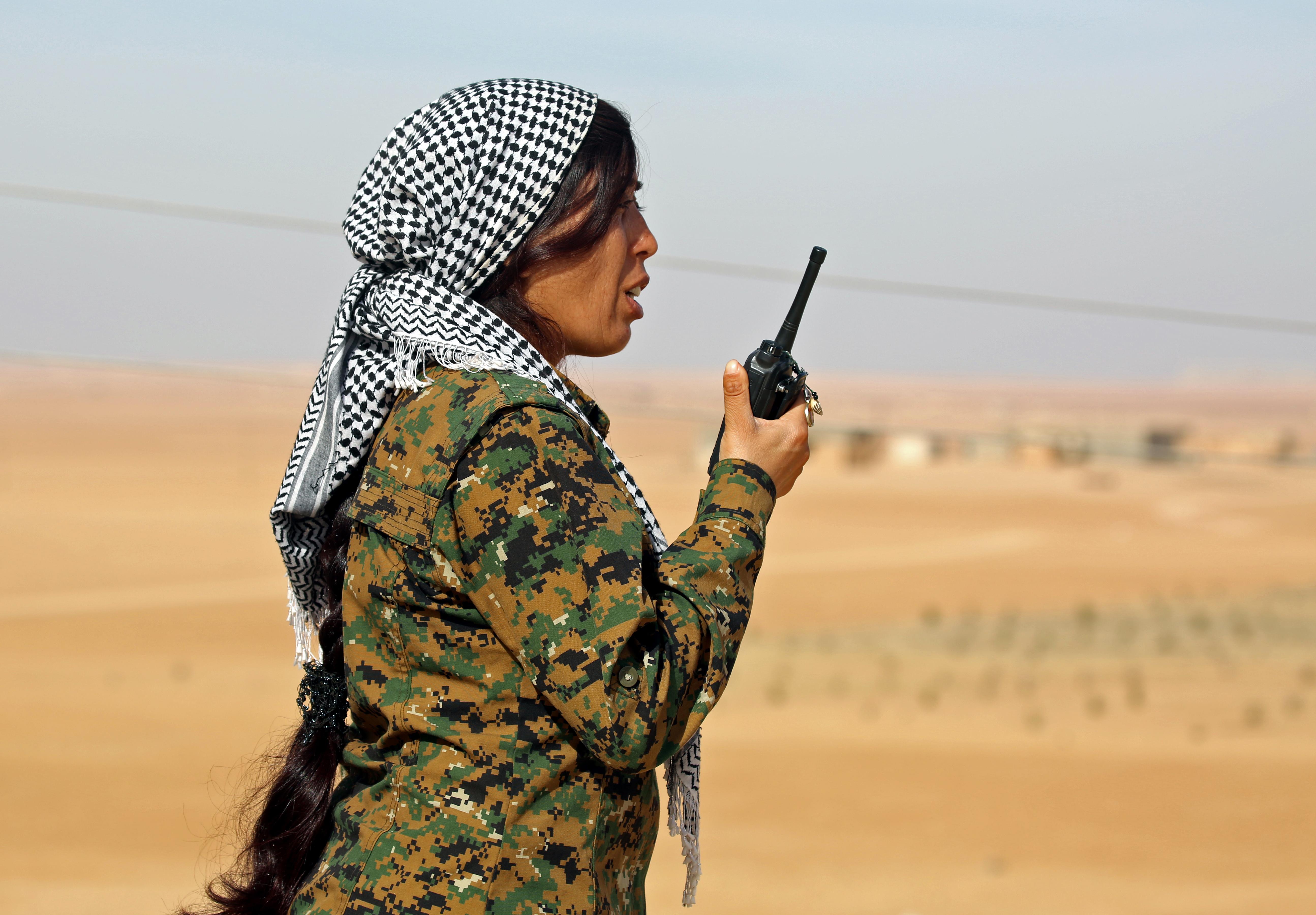 مقاتلة كردية تتحدث عبر جهاز اللاسلكي