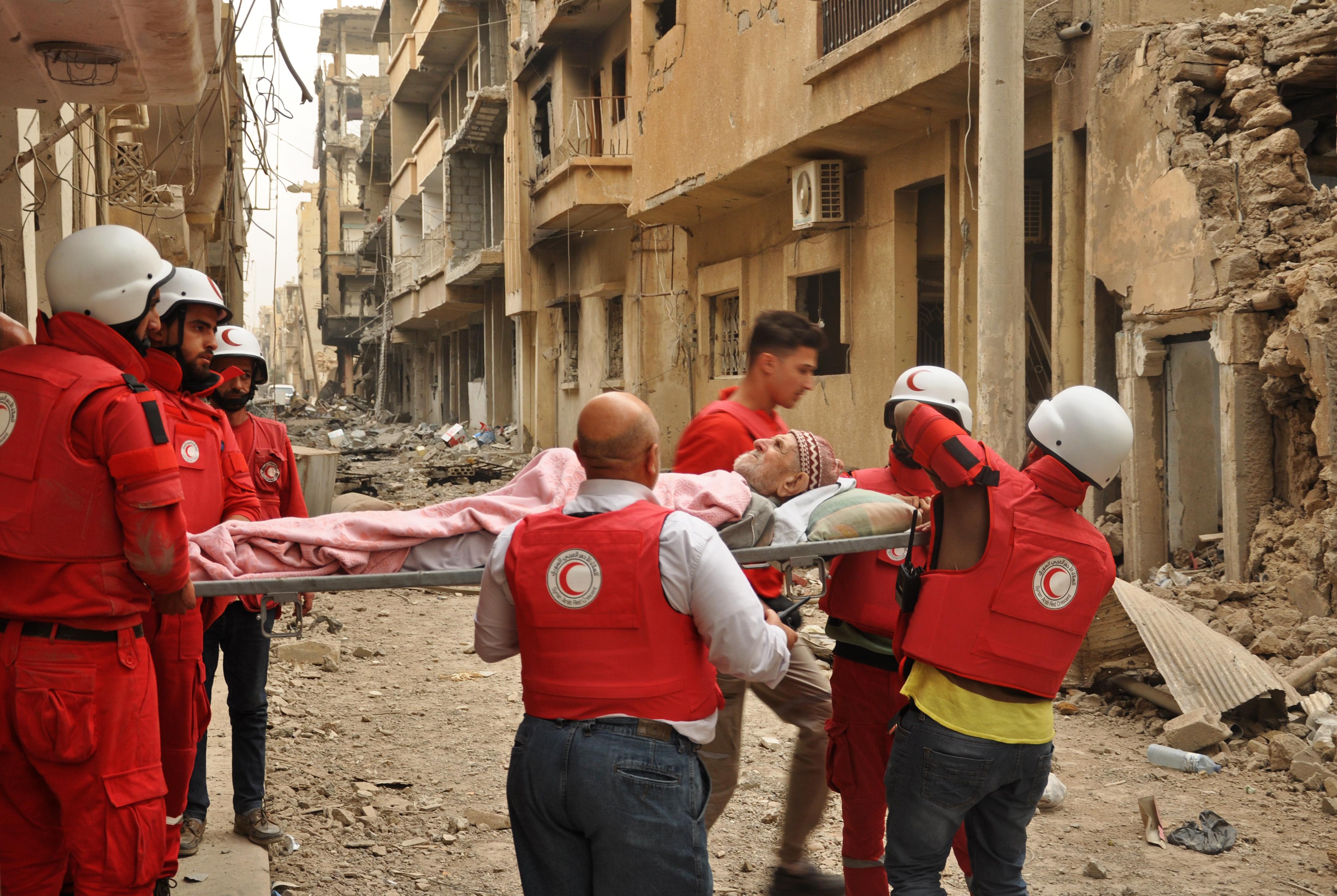 عناصر من الهلال الأحمر السوري يحملون أبو محمود