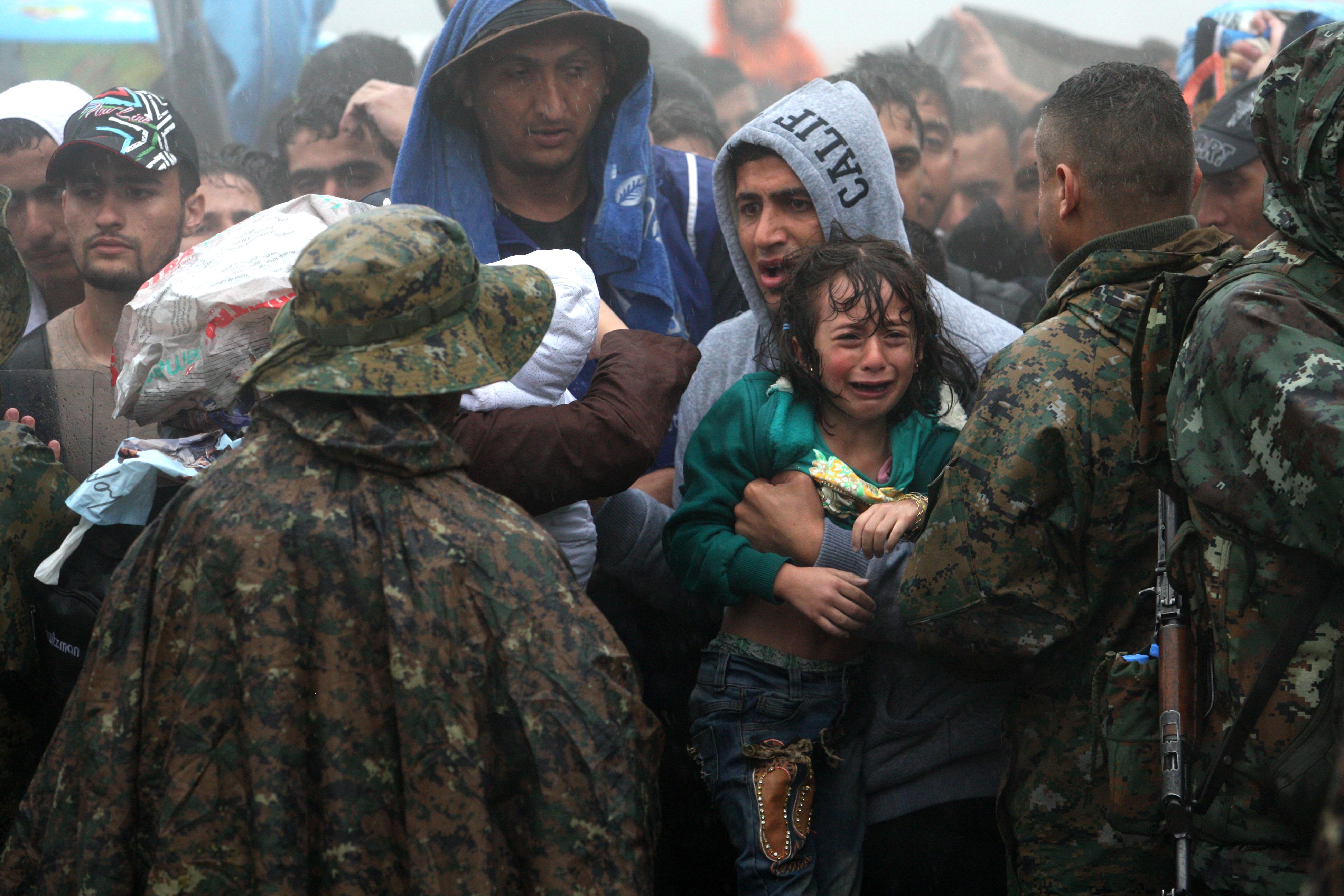 لاجئون ينتظرون تحت الأمطار لعبور الحدود اليونانية - المقدونية