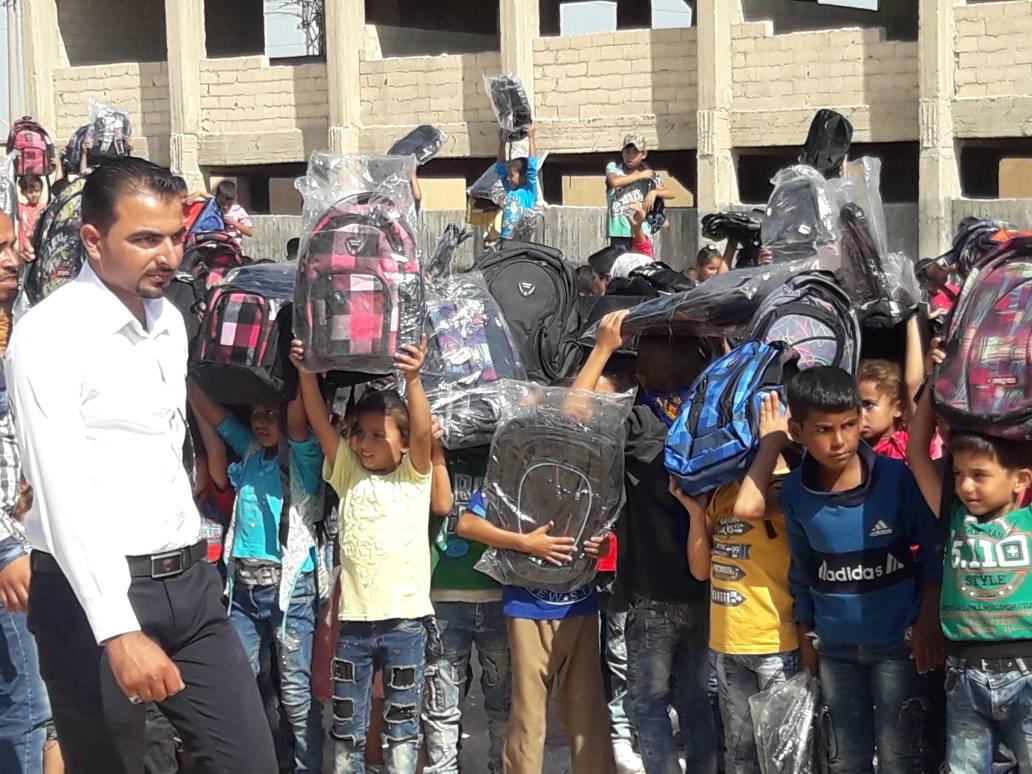 توزيع حقائب مدرسية على بعض التلاميذ لتشجيعهم على الذهاب إلى المدرسة في مدينة الرقة