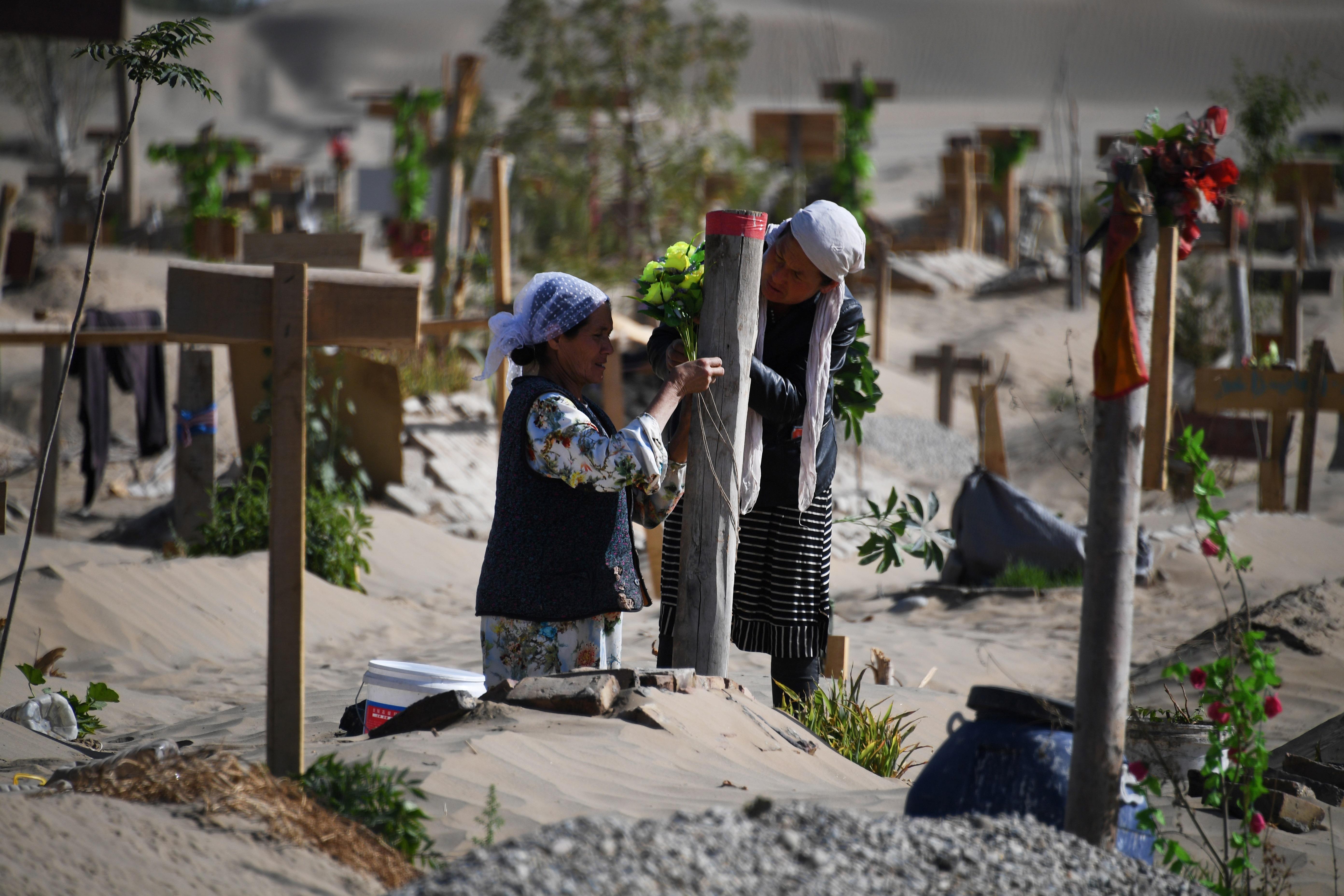 سيدتان من الأويغور أمام قبر قريب لهما