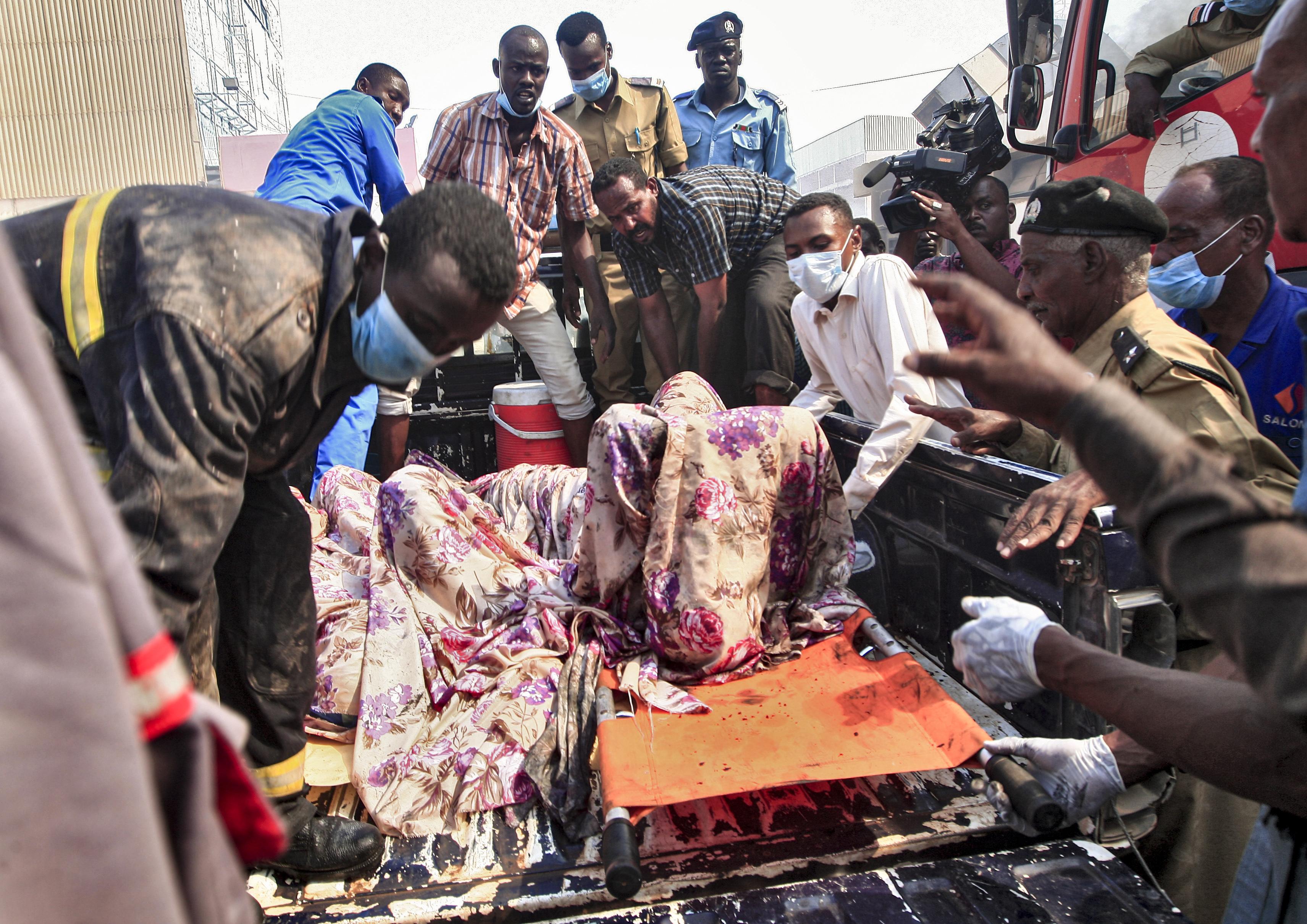 عناصر من الدفاع المدني السوداني يحملون جثامين ضحايا الحريق في المنطقة الصناعية شمال الخرطوم