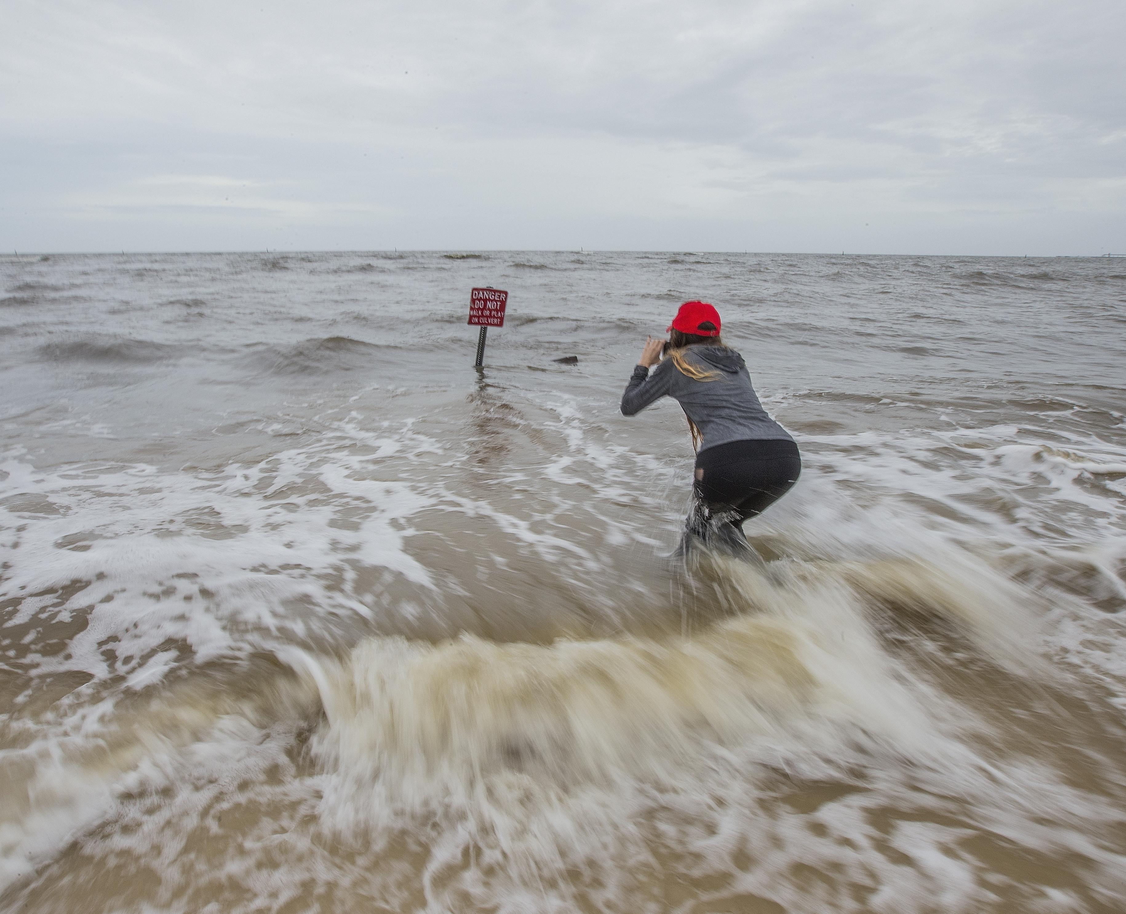 امرأة تصور علامة الخطر الموجودة في إحدى نقاط ساحل ولاية مسيسيبي