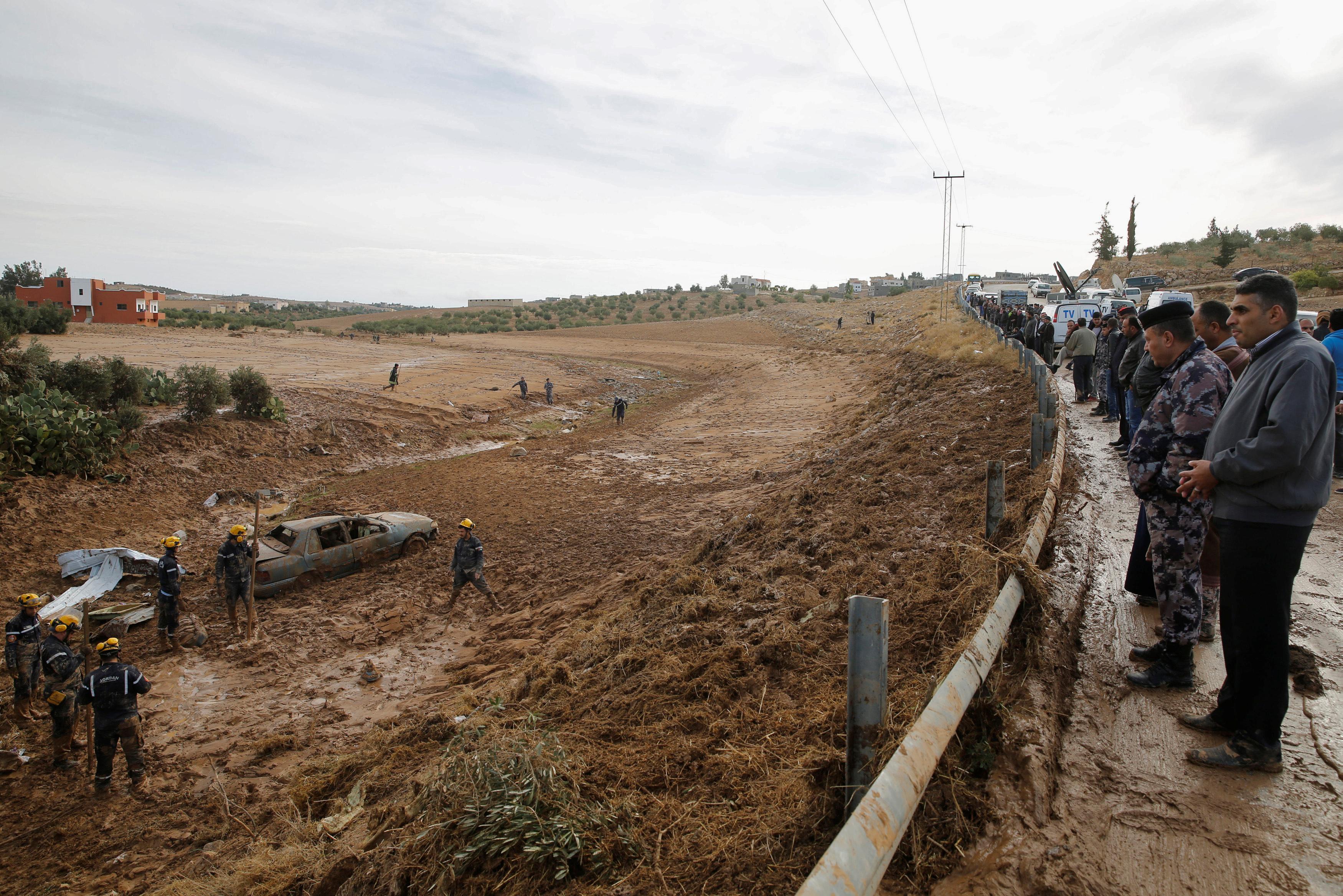 أناس يشاهدون عناصر الدفاع المدني الأردني أثناء بحثه عن مفقودين