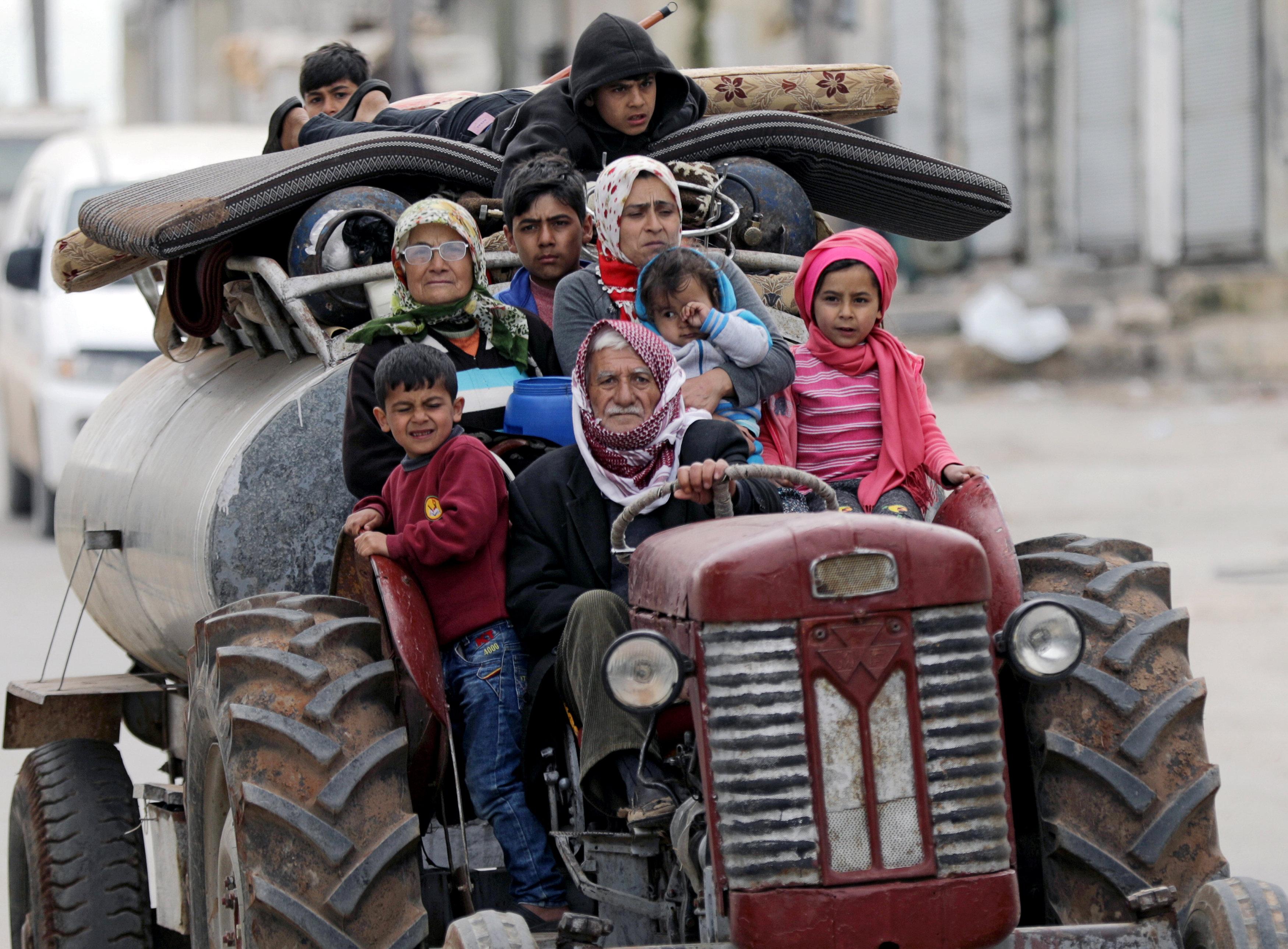 عائلة سورية تستخدم الجرار الزراعي للرحيل عن منزلها هربا من القصف التركي في عفرين