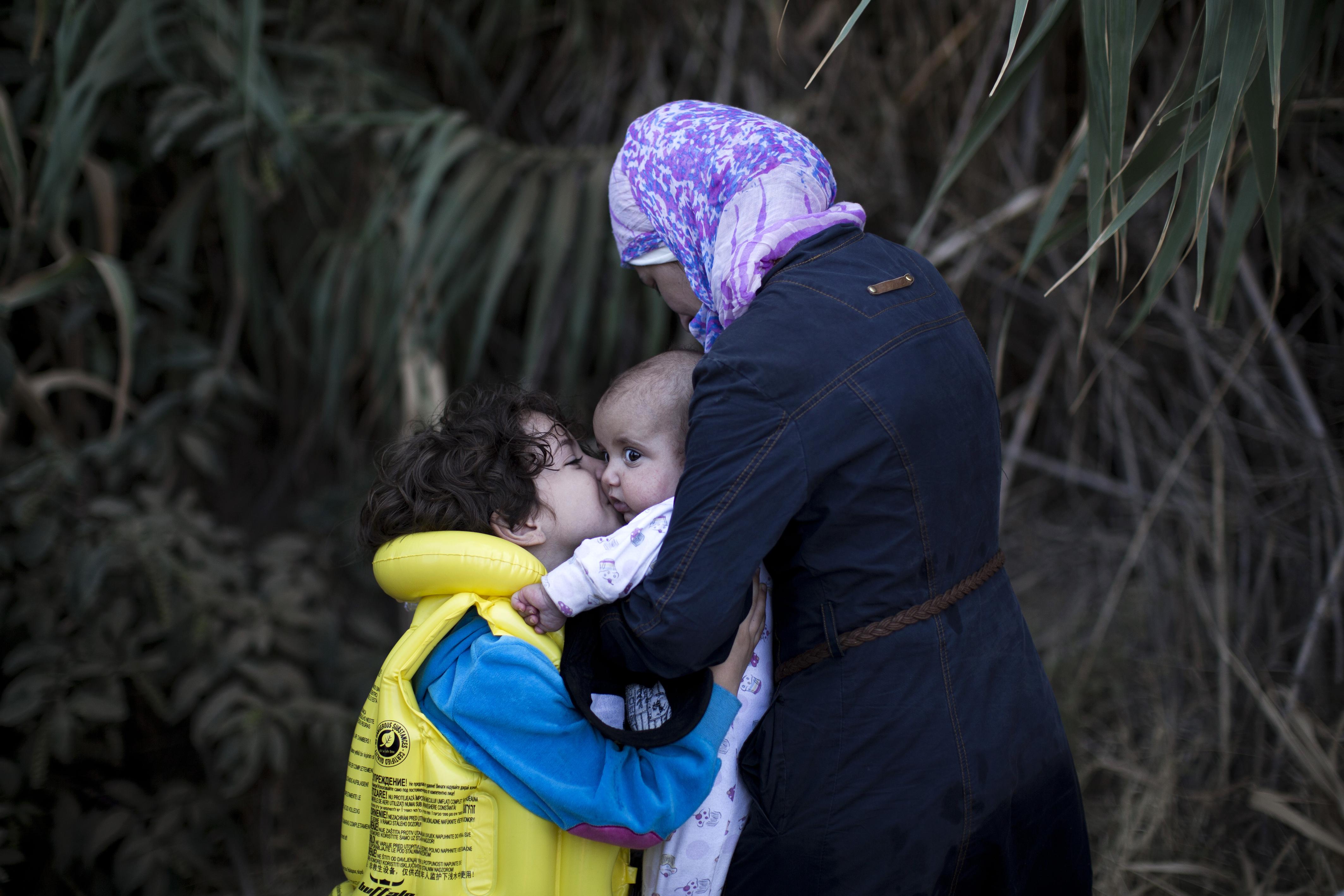 أم وطفلاها بعد وصولم إلى جزيرة ليسبوس اليونانية قادمين من تركيا