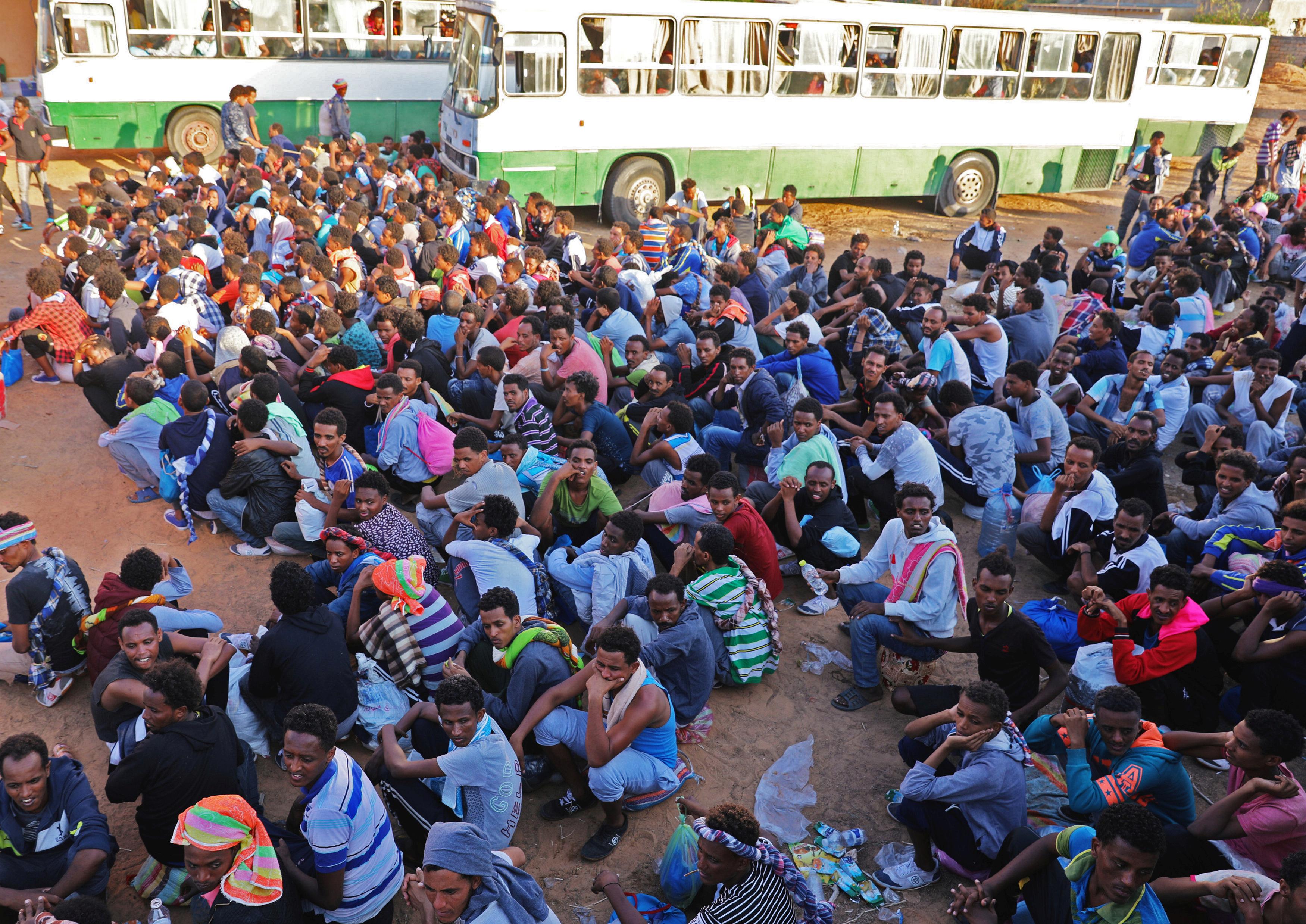 مهاجرون ينتظرون إعادة توزيعهم بعد إخلائهم من مركز آخر بسبب الاشتباكات وإصابة بعضهم