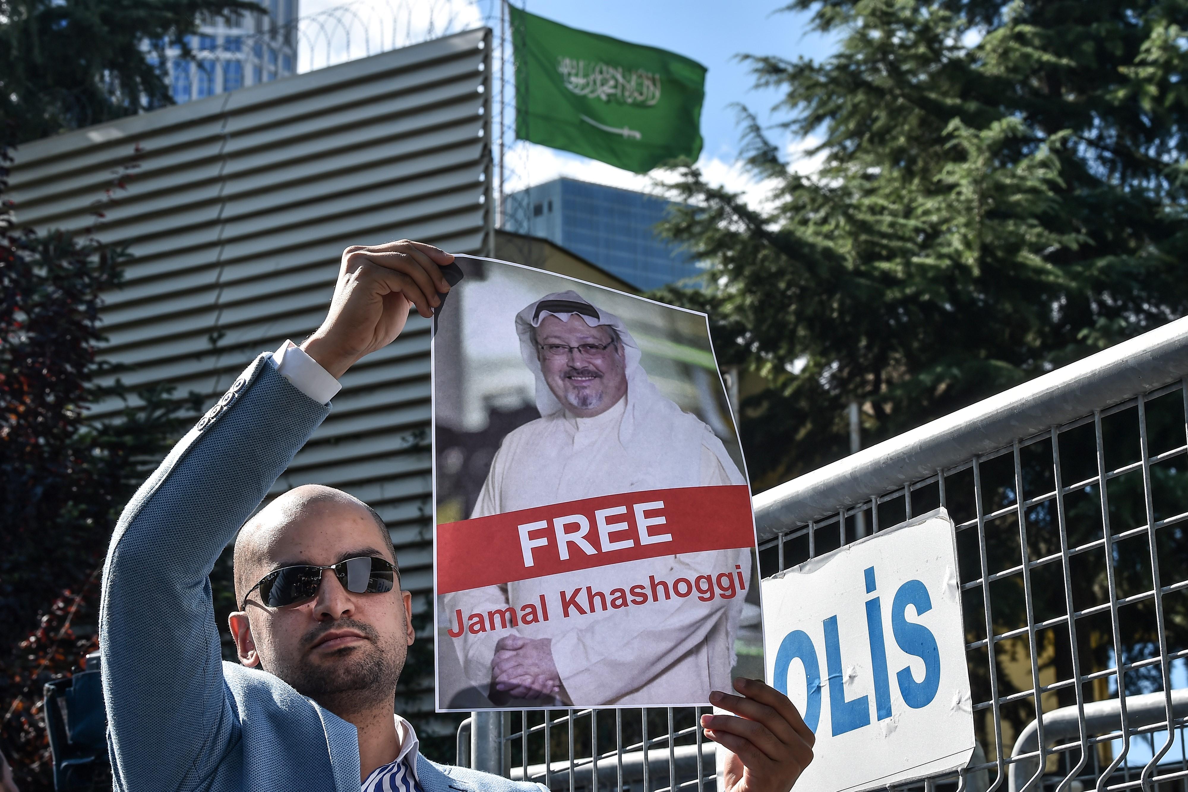 متضامن يقف أمام القنصلية السعودية في اسطنبول حاملا صورة الصحافي جمال خاشقجي