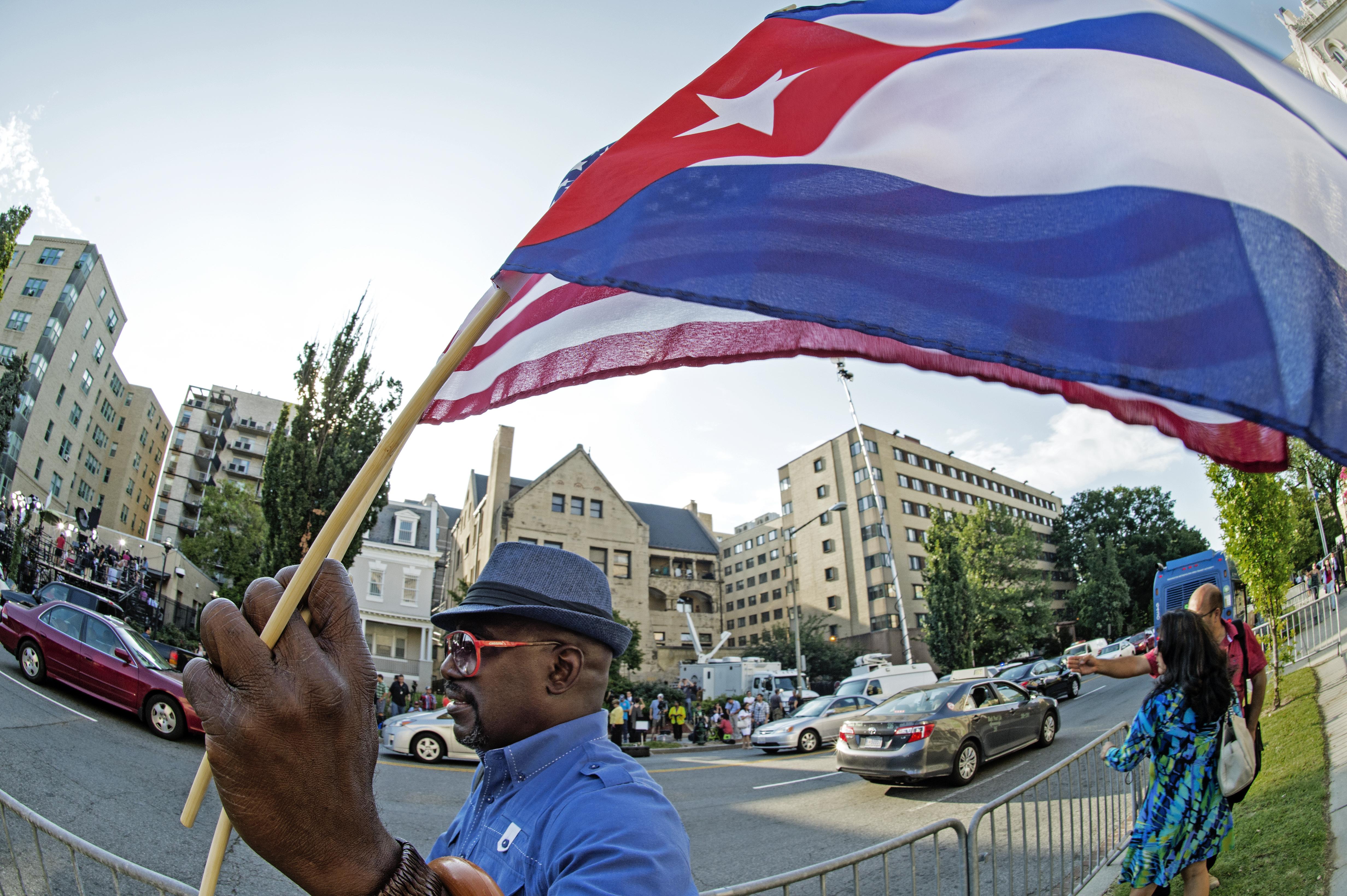 رجل يحمل العلمين الأميركي والكوبي قرب مقر البعثة الدبلوماسية الكوبية في واشنطن