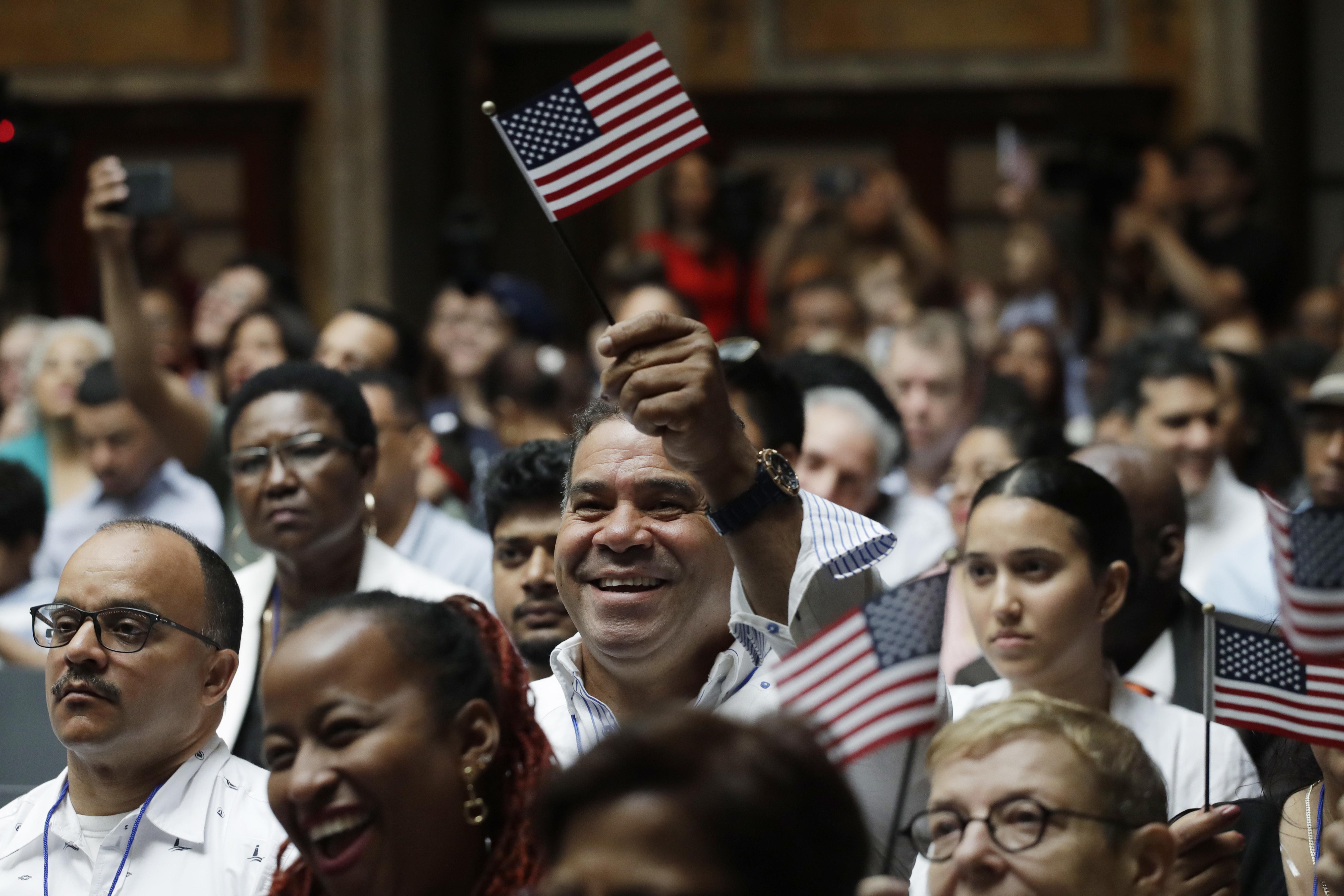 مواطنون جدد يلوحون بعلم الولايات المتحدة خلال مراسم في نيويورك