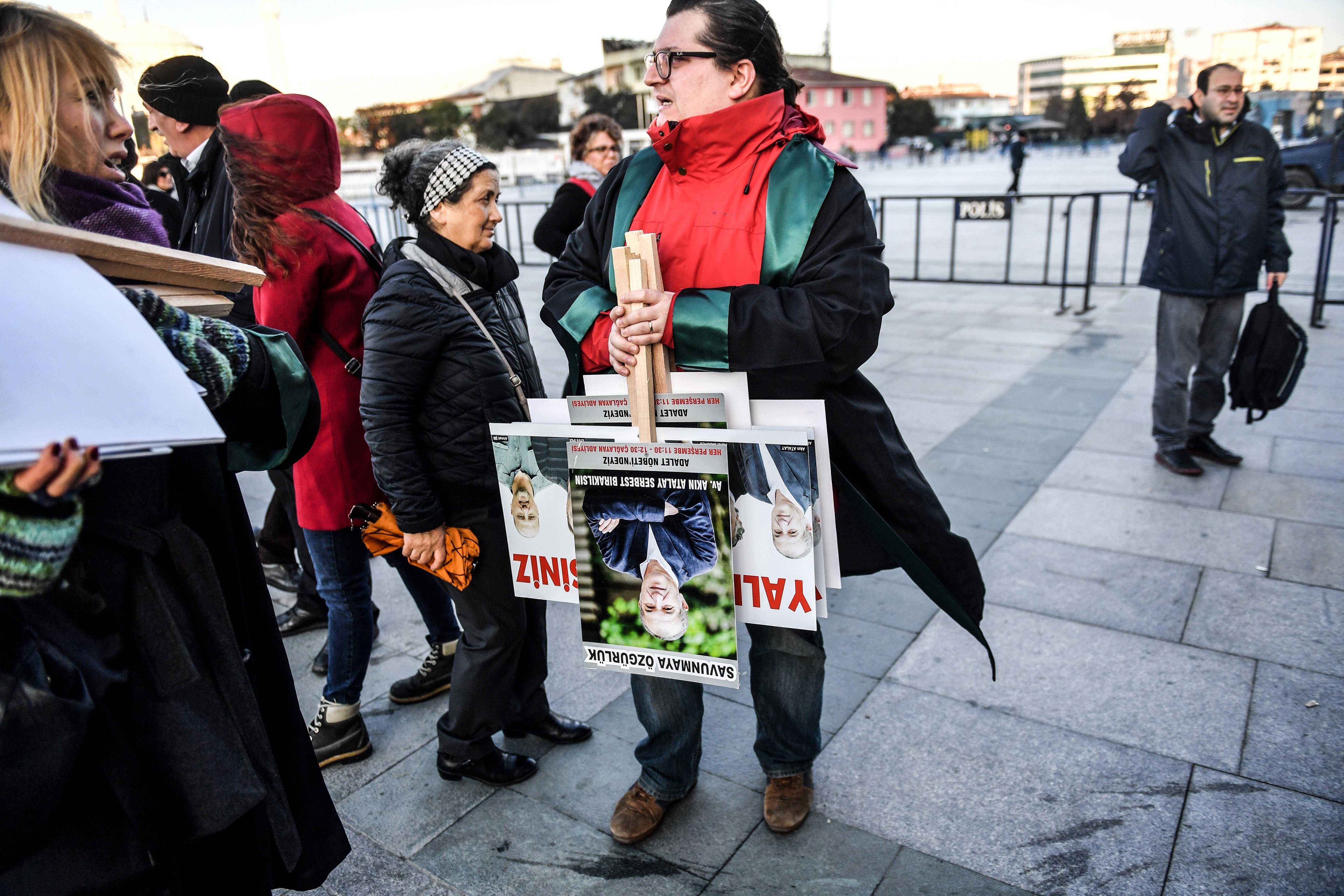 سيدة تحمل صورا لصحافيين من صحيفة 'جمهورييت' يحاكمون بتهم 'الإرهاب'