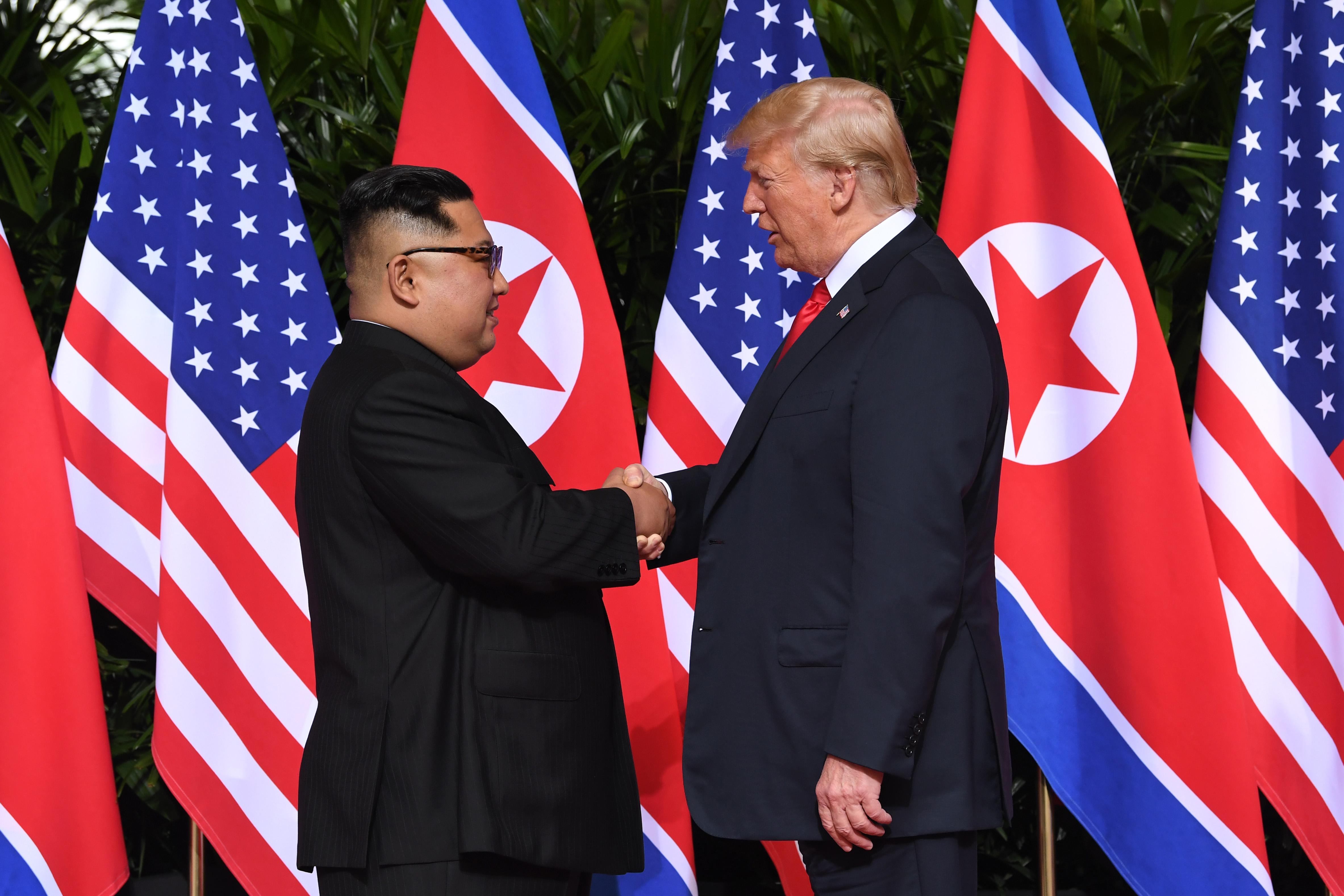 الرئيس دونالد ترامب يصافح زعيم كوريا الشمالية كيم جونغ أون في بداية لقائهما التاريخي في سنغافورة