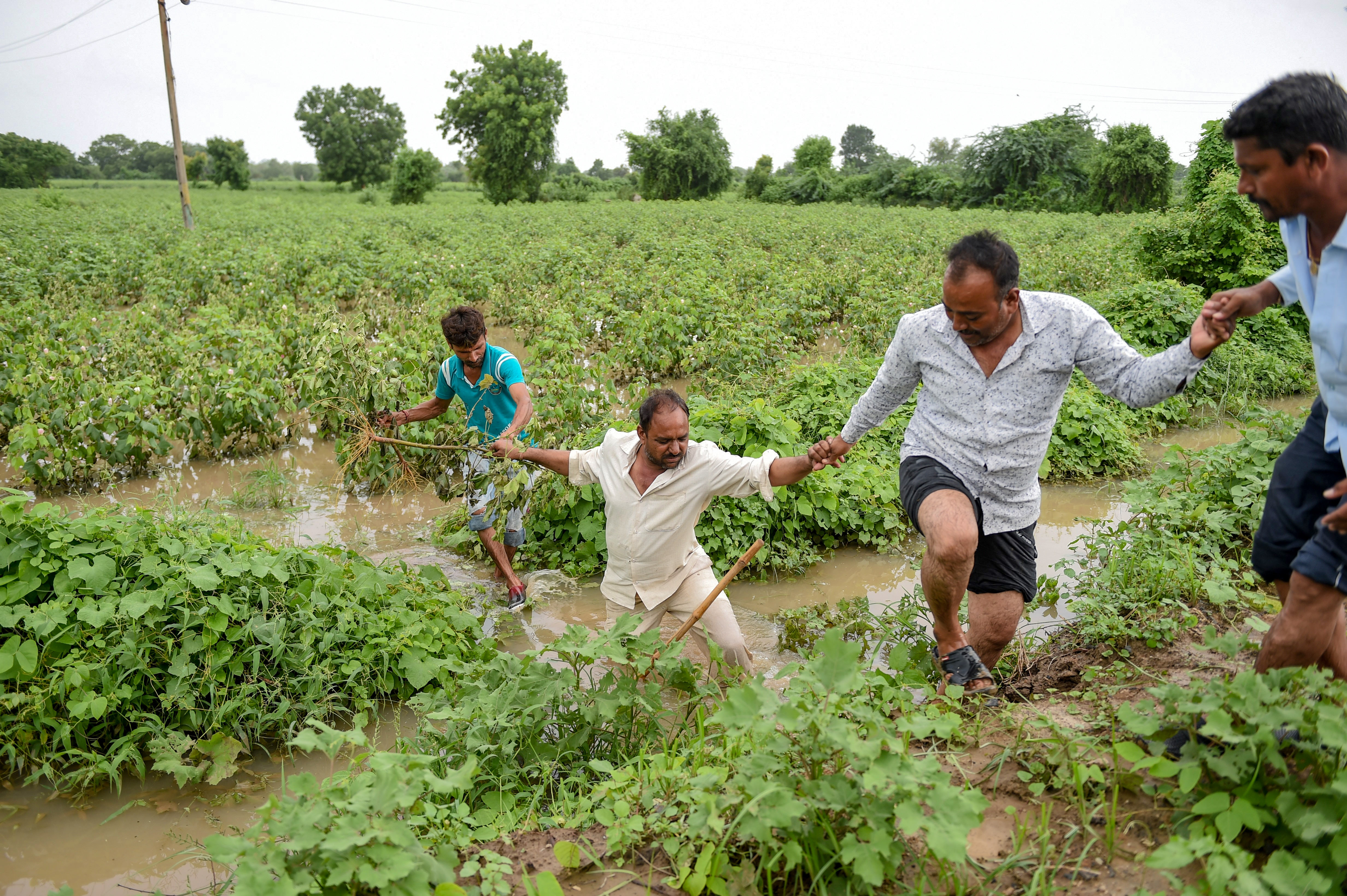 مواطنون يحاولون الابتعاد عن المناطق التي غمرتها مياه الأمطار والفيضانات