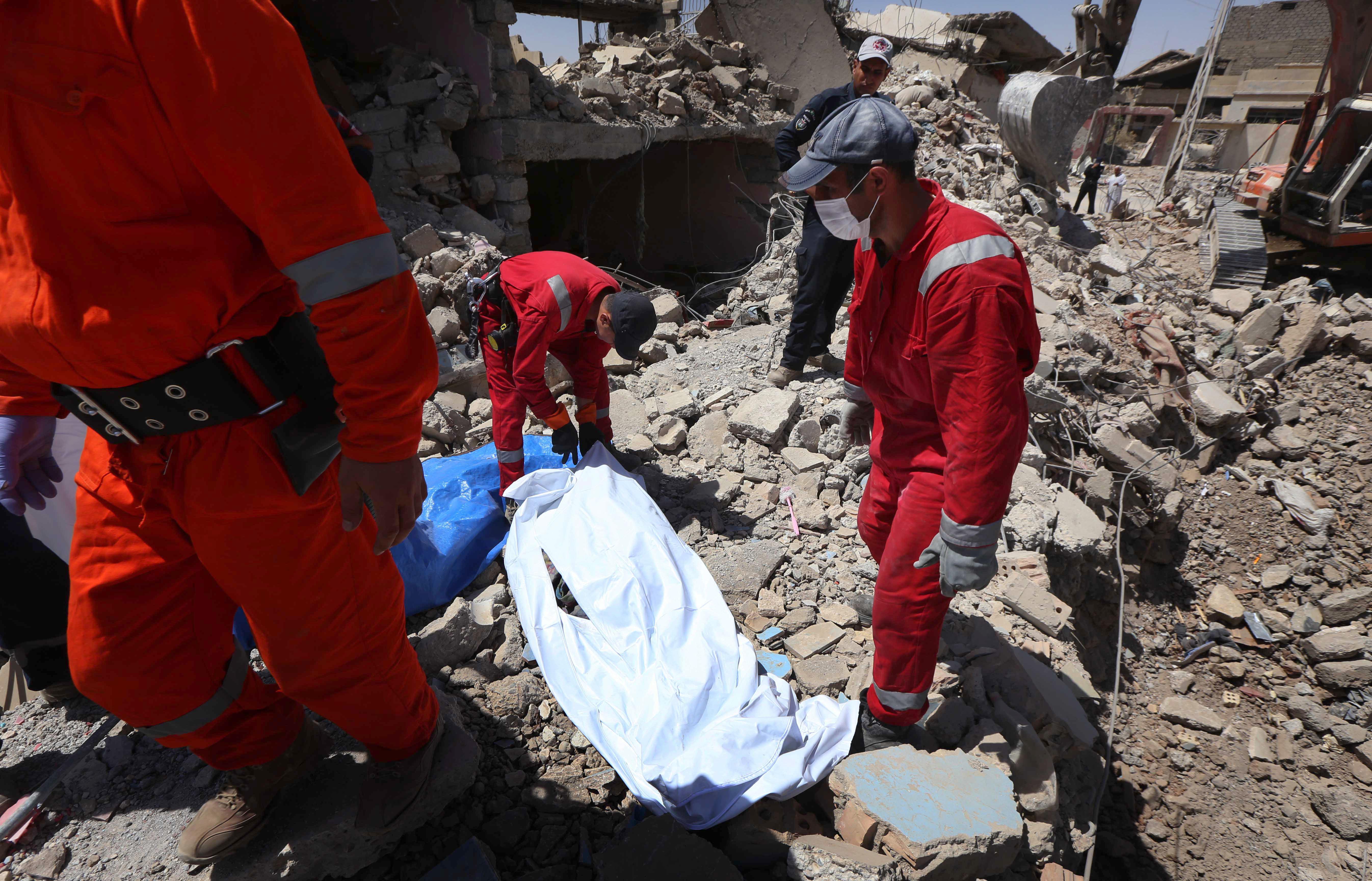 عناصر في الدفاع المدني بعد استخراج جثة كانت تحت الأنقاض في الموصل