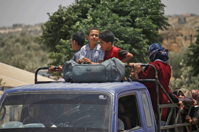 أطفال سوريون يستقلون شاحنة خلال النزوح عن ديارهم