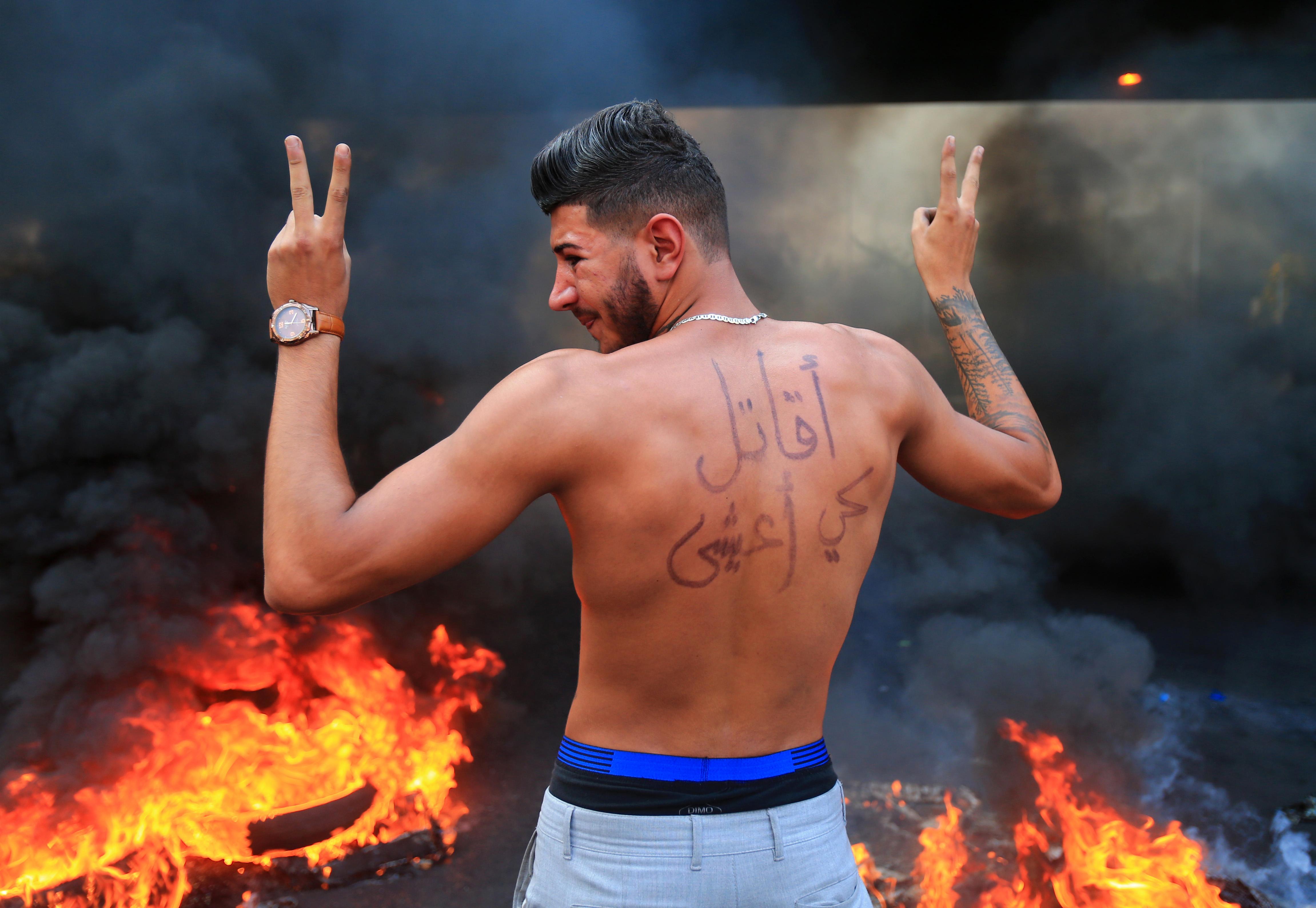 """متظاهر في لبنان كتب على ظهره: """"أقاتل كي أعيش"""""""