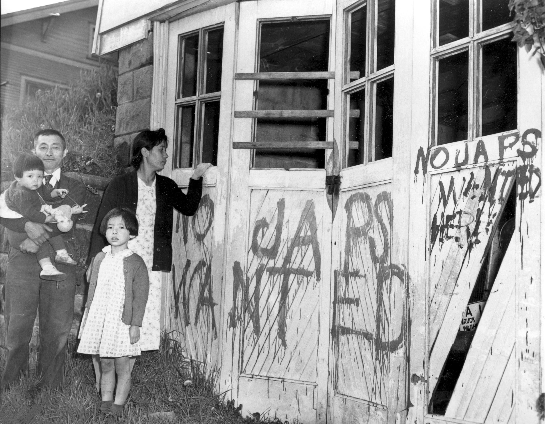 """أسرة يابانية بعد عودتها من مخيم احتجاز في هانت بأيداهو إلى منزلها الذي تعرض للتخريب وكتب عليه """"غير مرغوب بأي يابانيين"""" في سياتل بواشنطن."""
