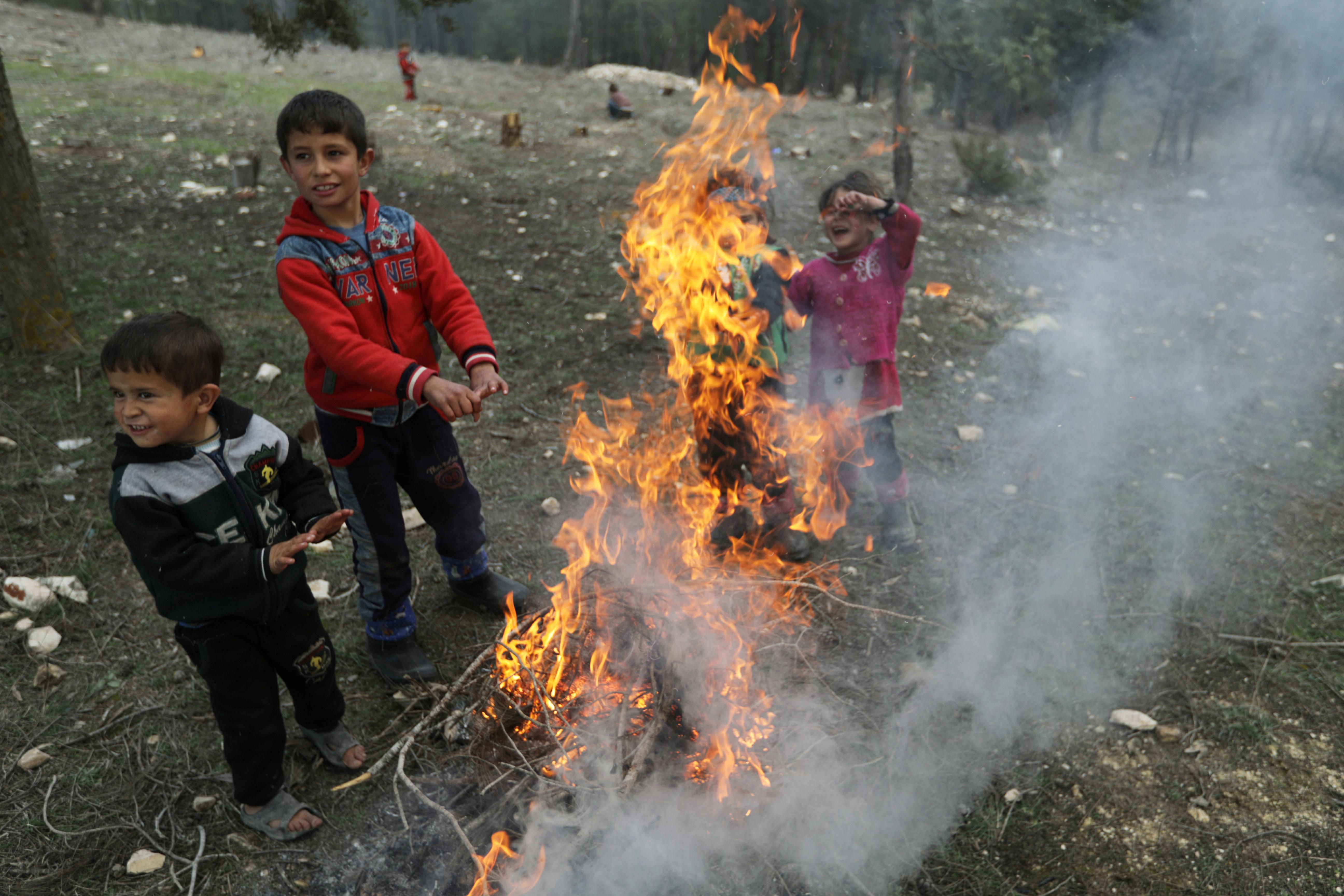 أطفال نازحون يحاولون تدفئة أجسادهم الصغيرة بعد فرارهم  والقصف في شمال غرب سوريا