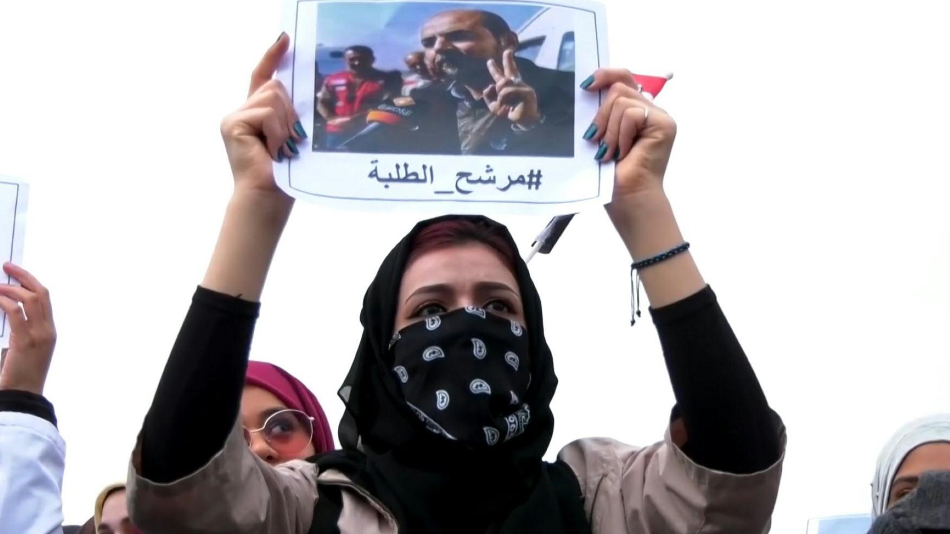 متظاهرة ترفع صورة الركابي