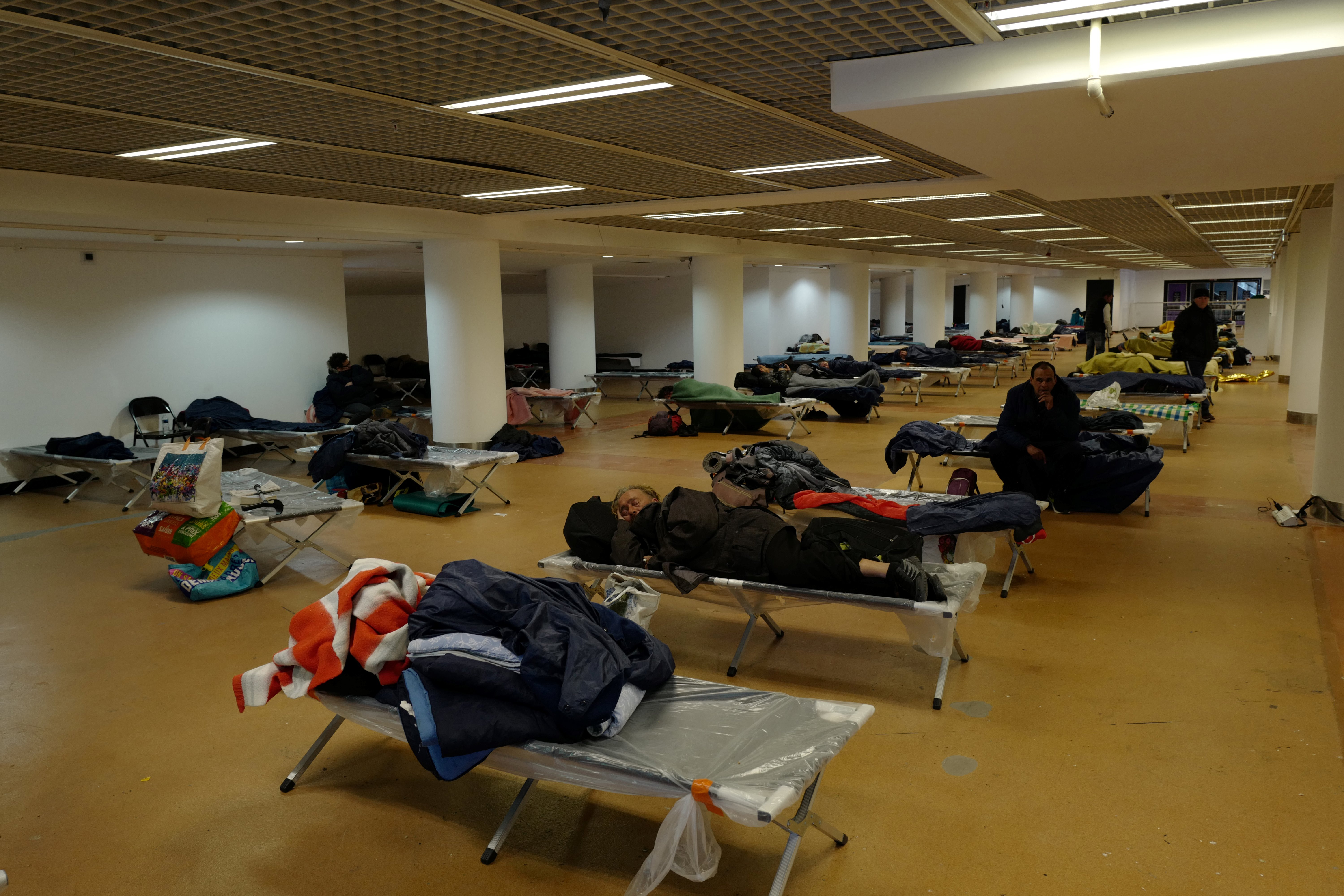 People rest inside the Festival Palace, on March 25, 2020 in Cannes, in an area reconverted into a shelter for homeless people,…