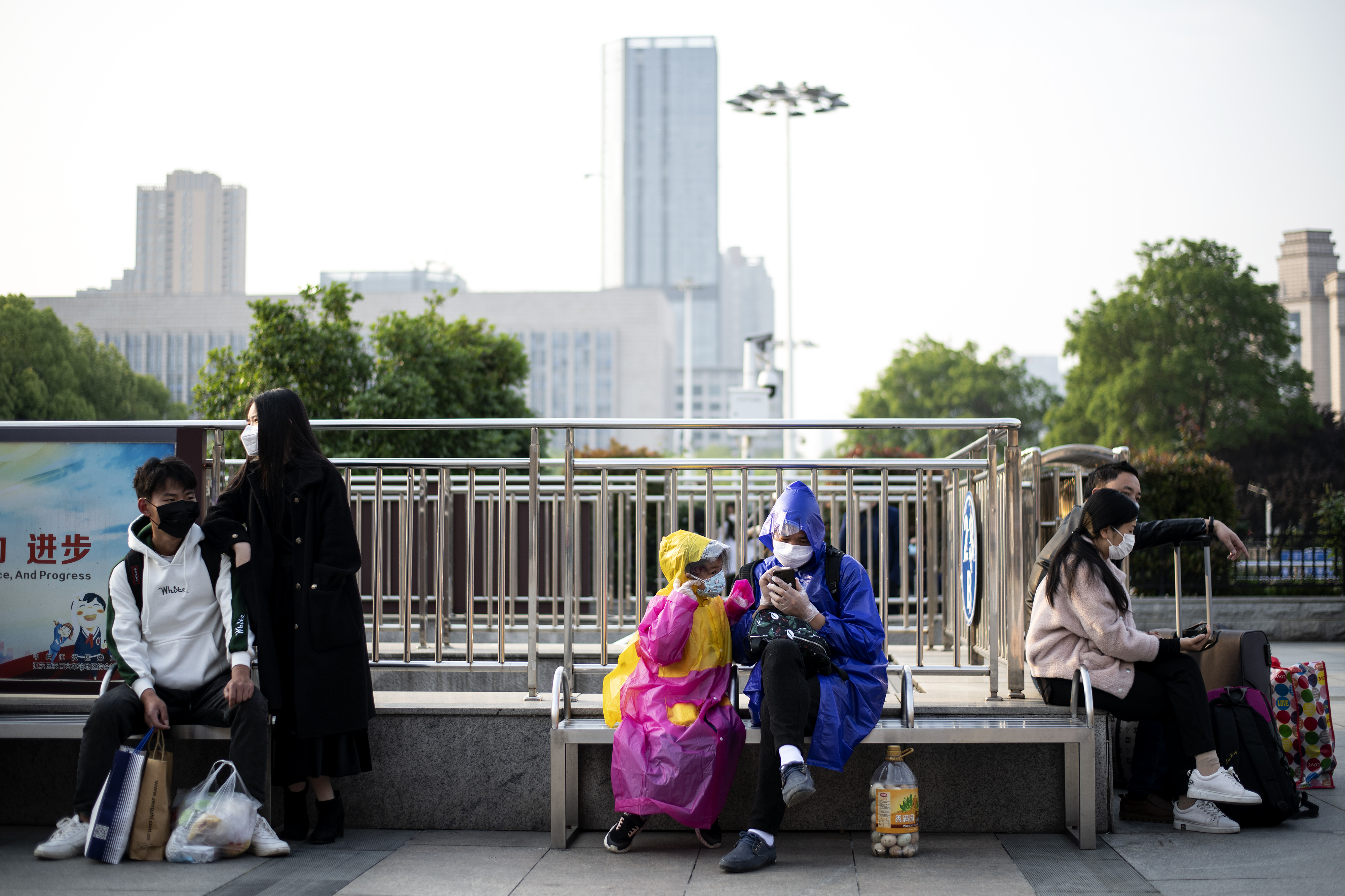 People wearing face masks sit outside Hankou Railway Station in Wuhan as people arrive in the hope of taking one of the first…