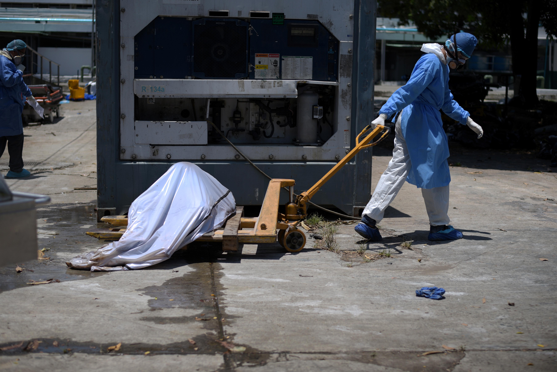عمال يحملون الجثث لوضعها في الحاويات