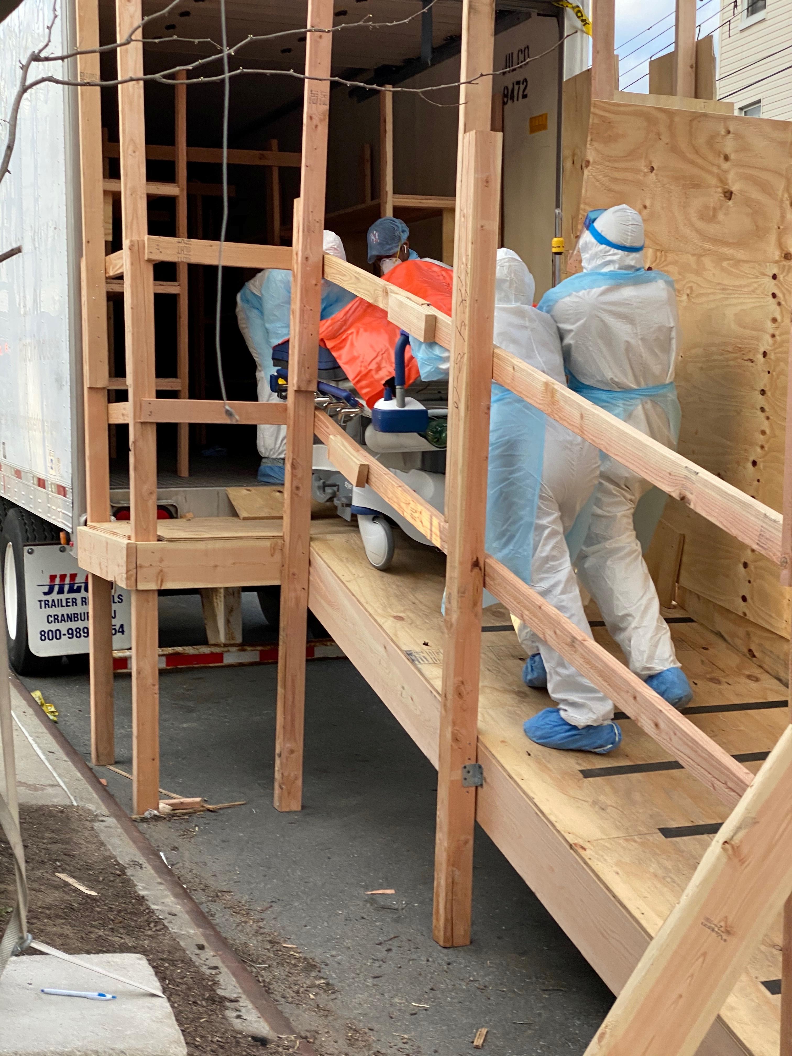 لحظة نقل الجثامين إلى عربة شاحنة التبريد
