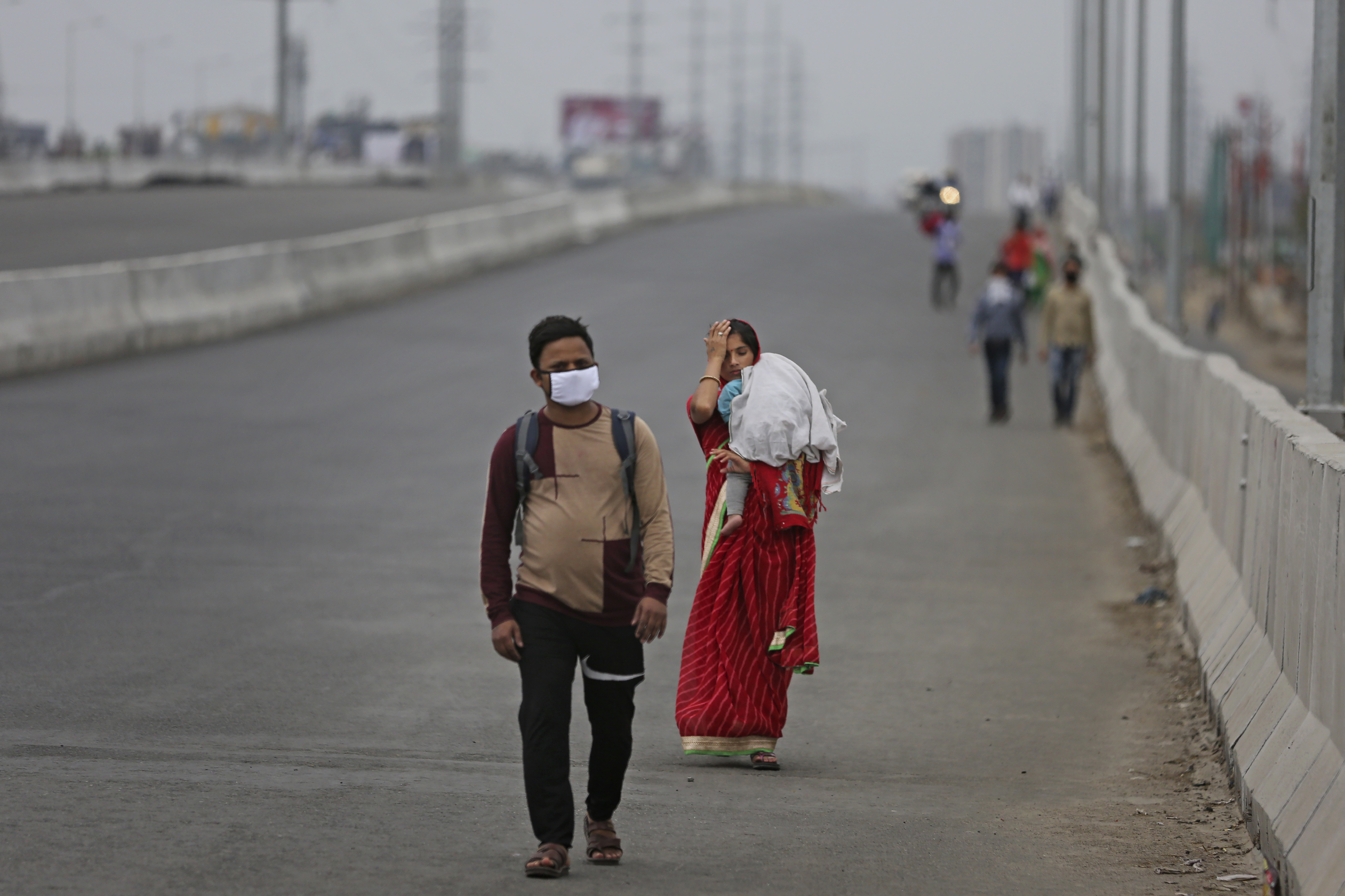 In this Thursday, March 26, 2020, file photo, an Indian couple carrying an infant walk along an expressway hoping to reach…
