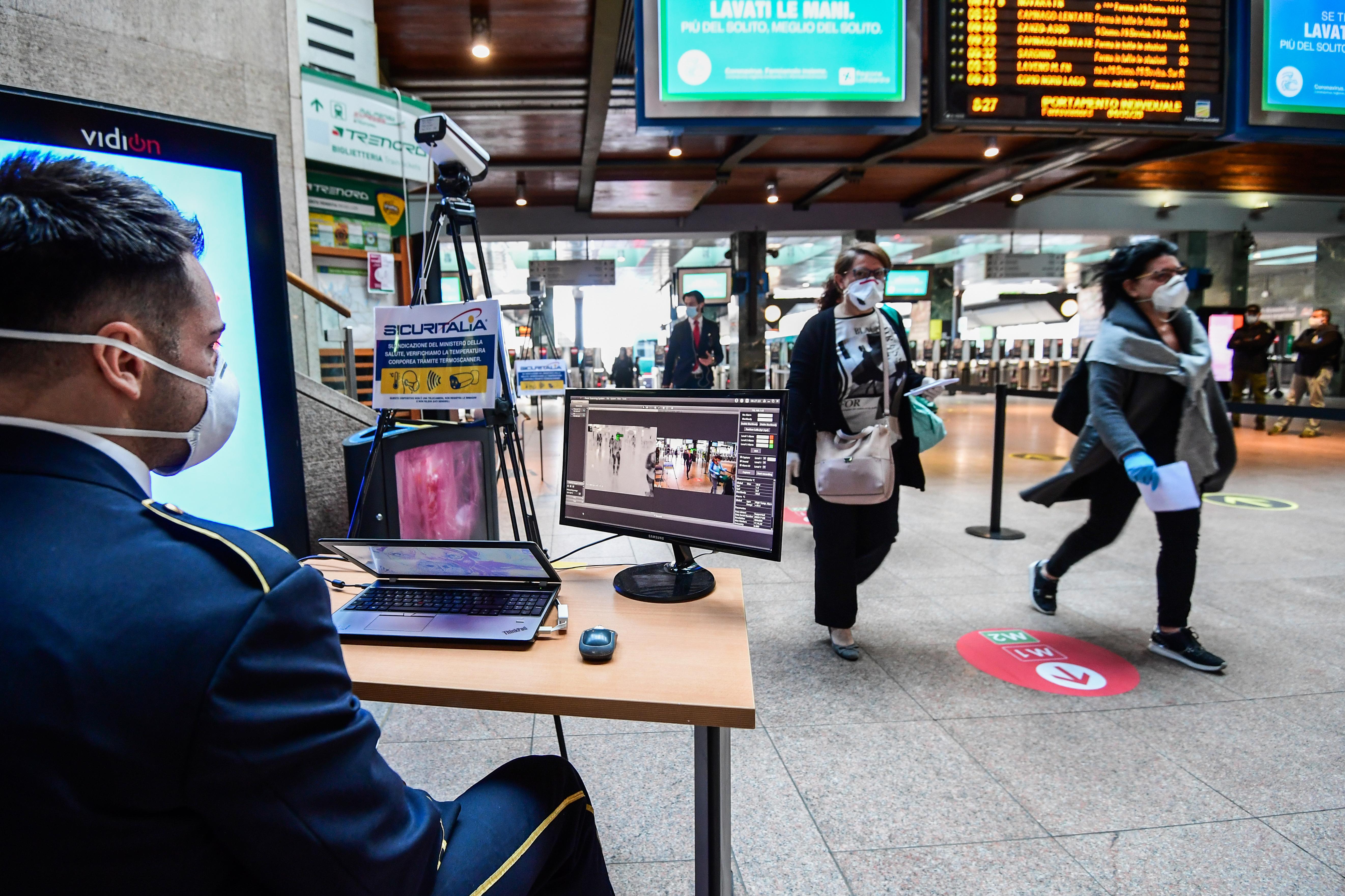 كاميران حرارية تفحص درجة حرارة جسم المسافرين عند العبور أمامها في ميلان بإيطاليا- 4 مايو 2020