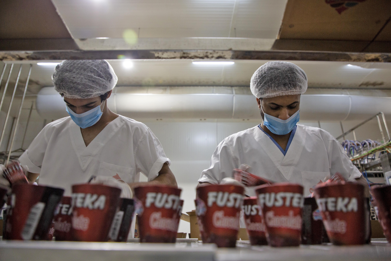 """عمال  يعبئون علب الآيس كريم في مصنع """"فستقة"""" للآيس كريم جنوب العراق"""