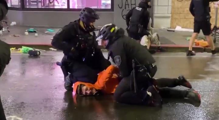 صورة من الفيديو الذي يظهر فيه شرطي وهو يضع ركبته على عنق متظاهر خلال اعتقاله في سياتل