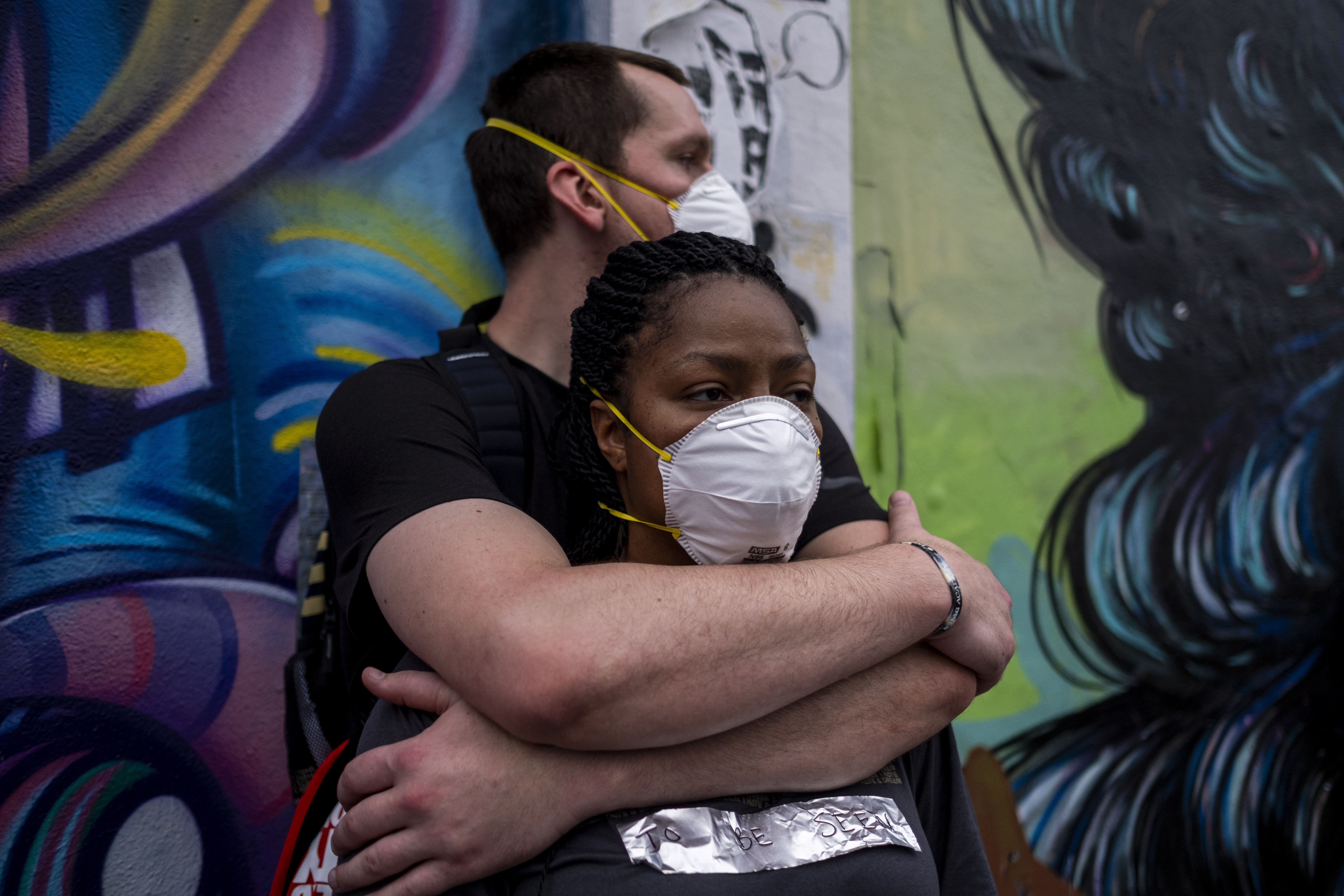 Protestors embrace during a rally in response to the recent death of George Floyd in Miami, Florida on June 2, 2020. (Photo by…