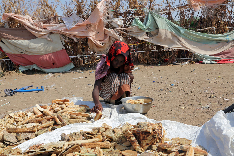فتاة يمنية فقيرة تبحث في القمامة عن قصاصات خبز تحفظ بها رمق عائلتها