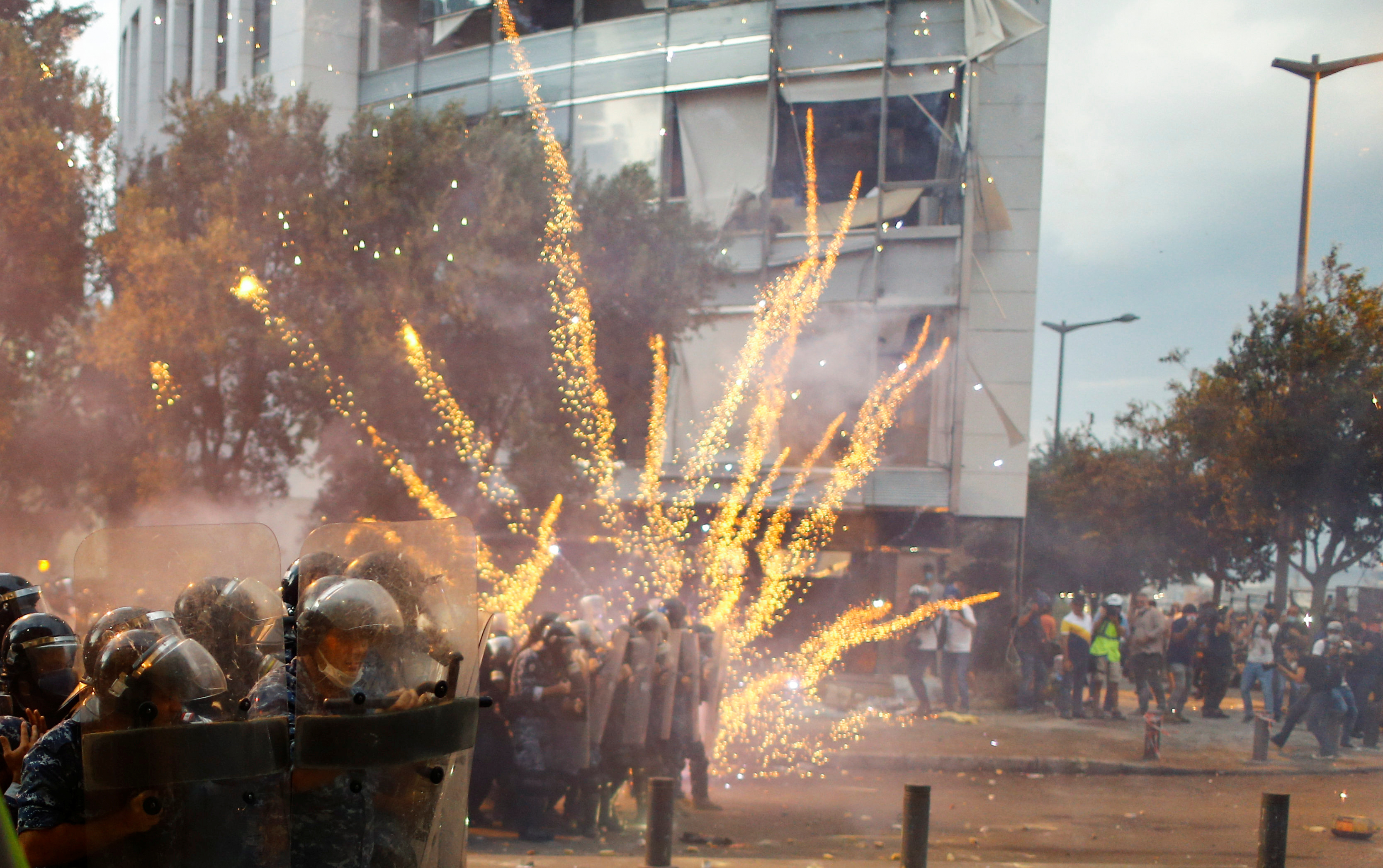 Fireworks are set off in front of police officers during anti-government protests that have been ignited by a massive explosion…