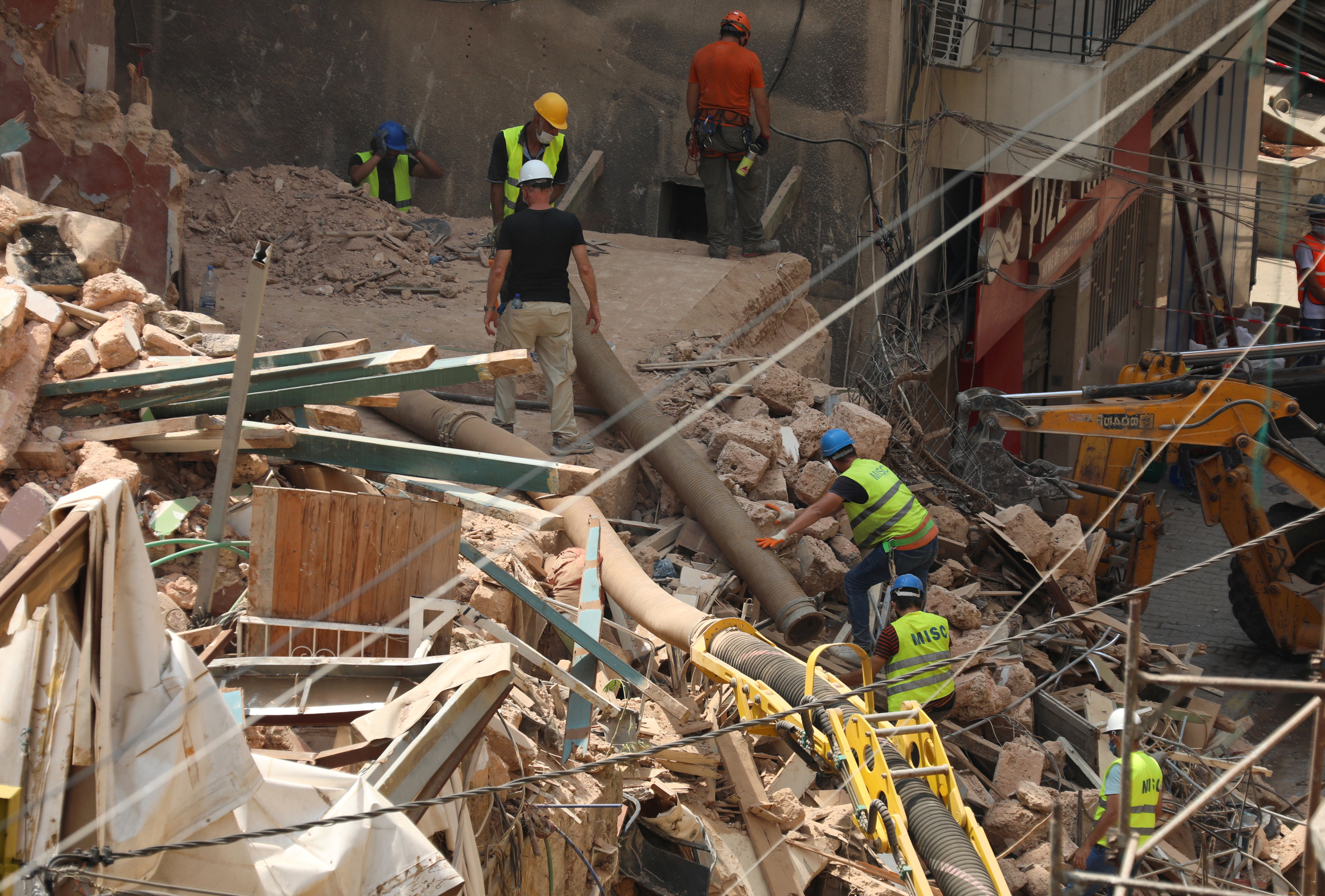 Volunteers and a member of the Chilean rescue team dig through the rubble of buildings which collapsed due to the explosion at…