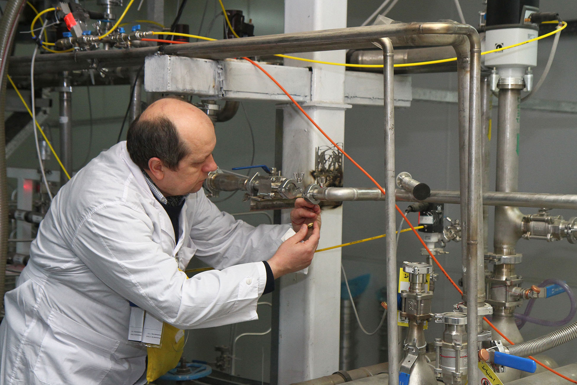 An unidentified International Atomic Energy Agency (IAEA) inspector disconnects the connections between the twin cascades for…