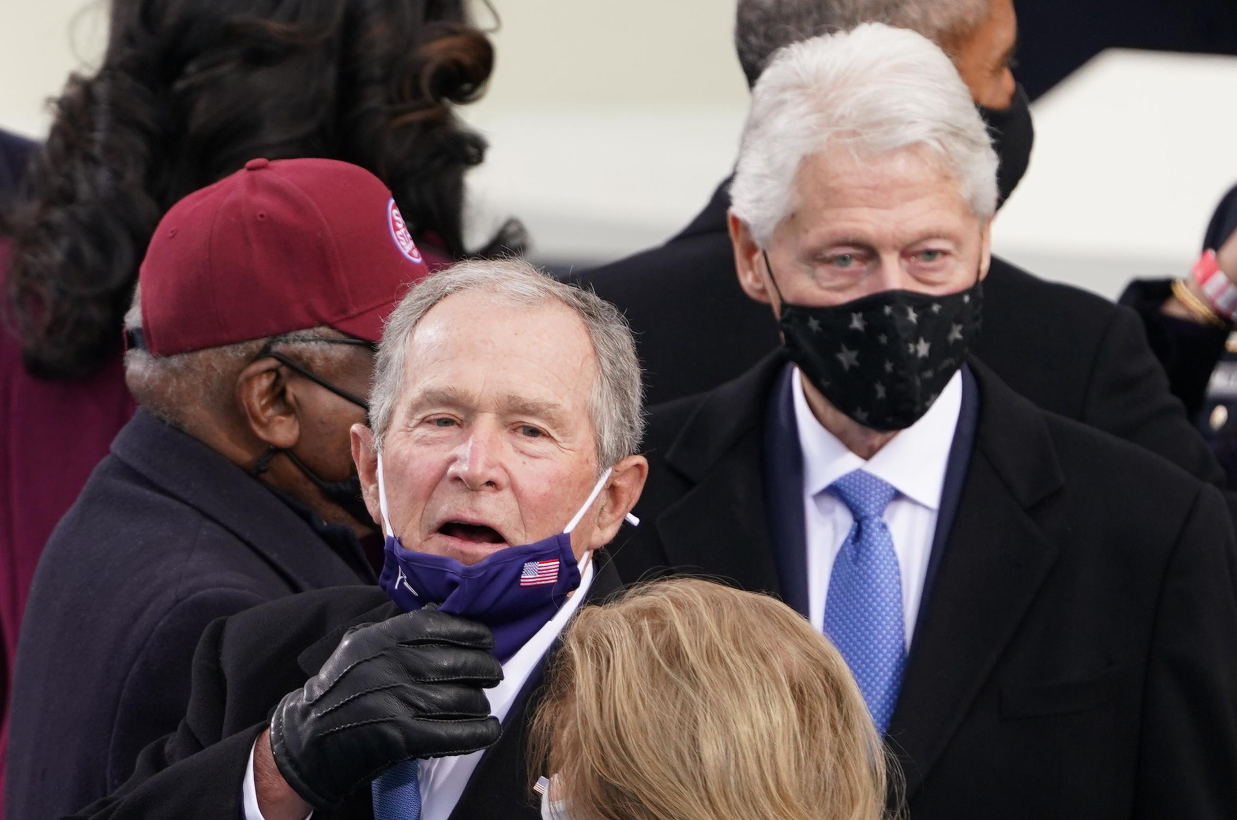 بدا بوش سعيدا ومبتسما في الحفل.. ويظهر إلى الخلف الرئيس الأسبق بيل كلينتون