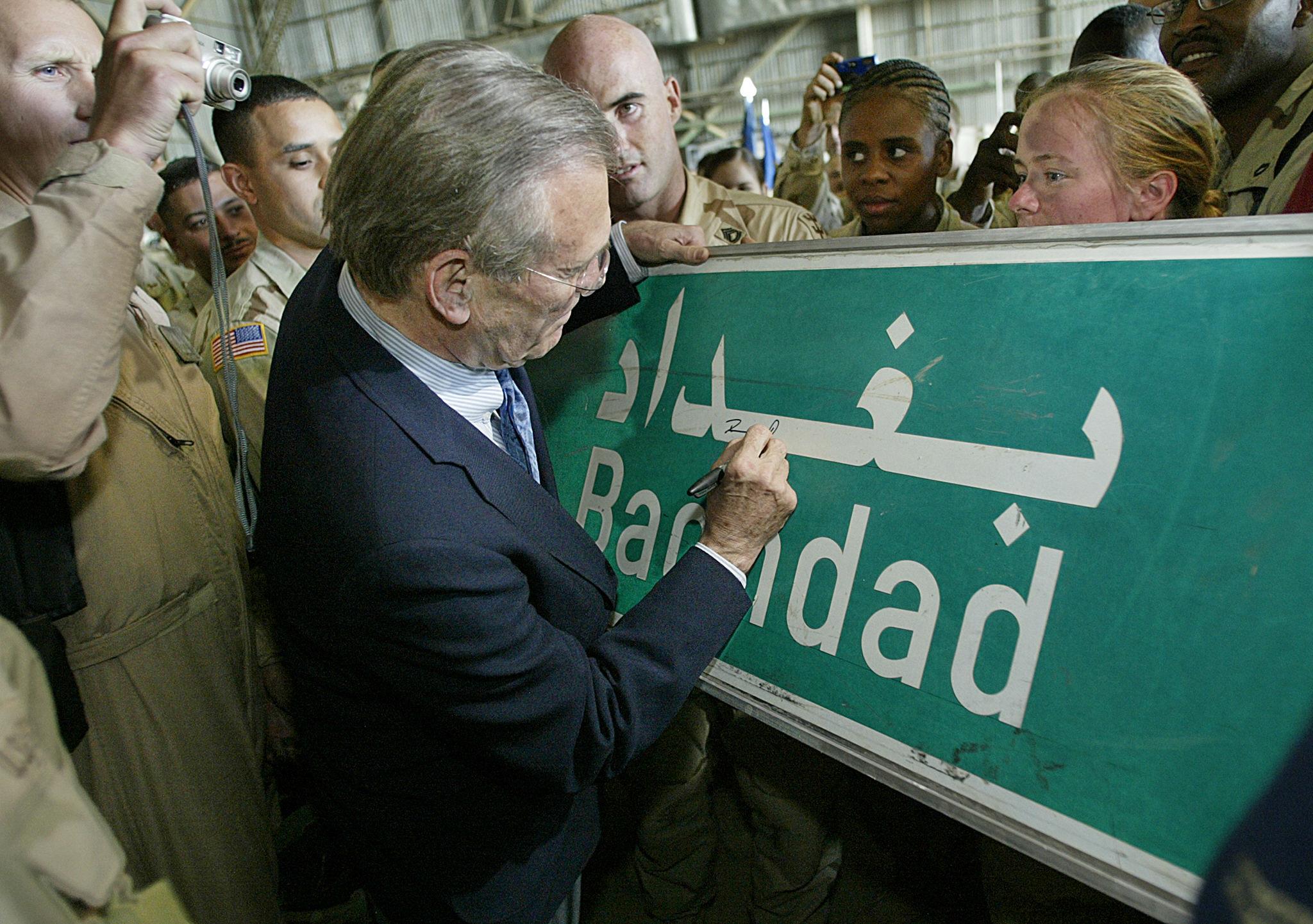 وزير الدفاع دونالد رامسفيلد يوقع على لوحة للجنود الأميركيين عام 2003. أرشيفية