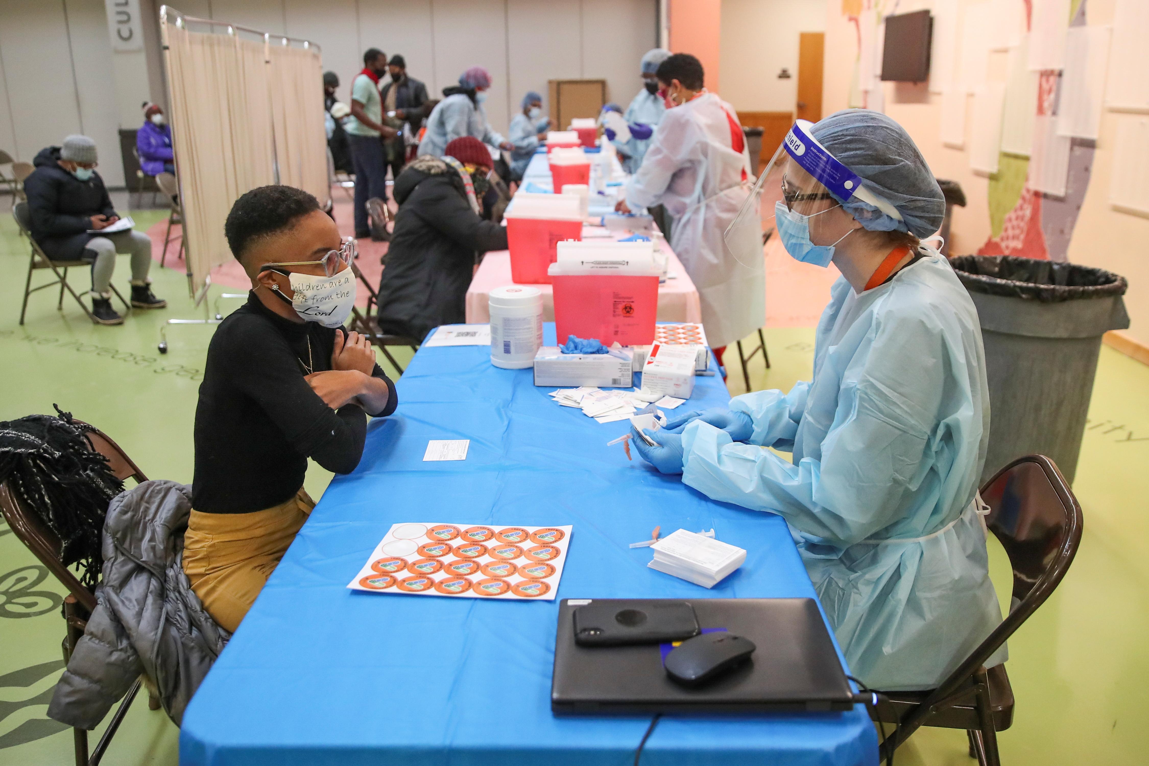 Stanisha Land (L) checks in with nurse Michelle Evers (R) before receiving the Moderna coronavirus disease (COVID-19)…
