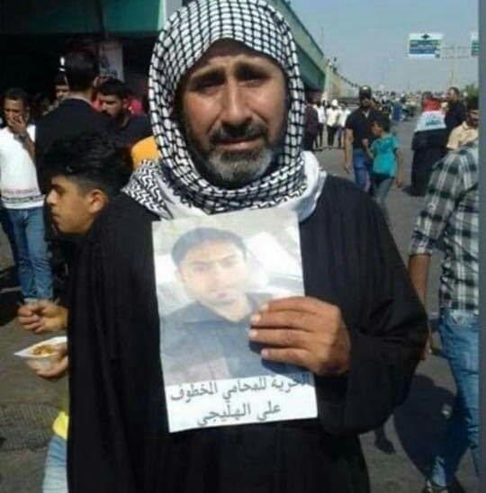 والد المحامي علي جاسب يحمل صورة ولده