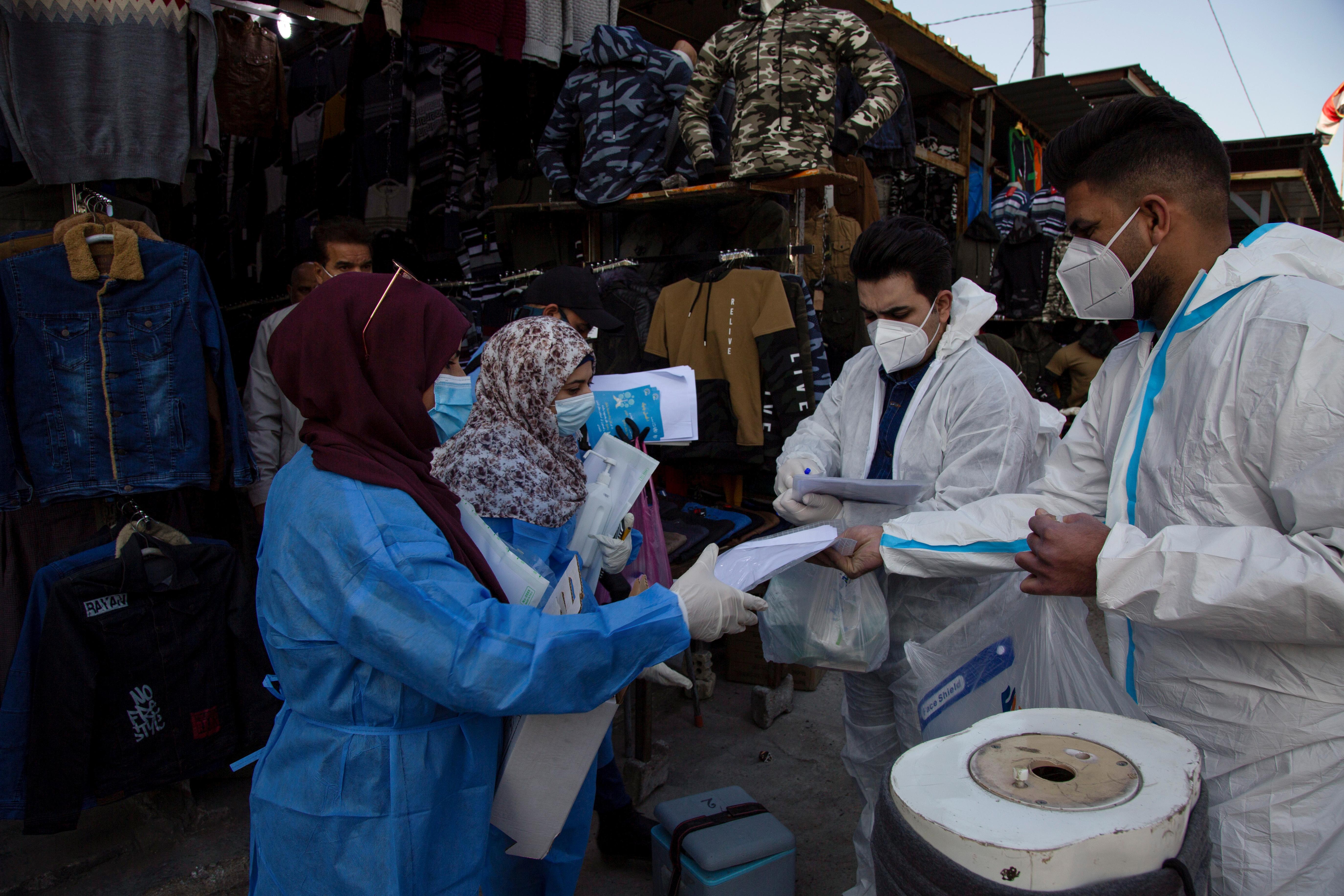 Members of medical team that work with mobile coronavirus disease (COVID-19) testing units prepare to take swabs from people in…