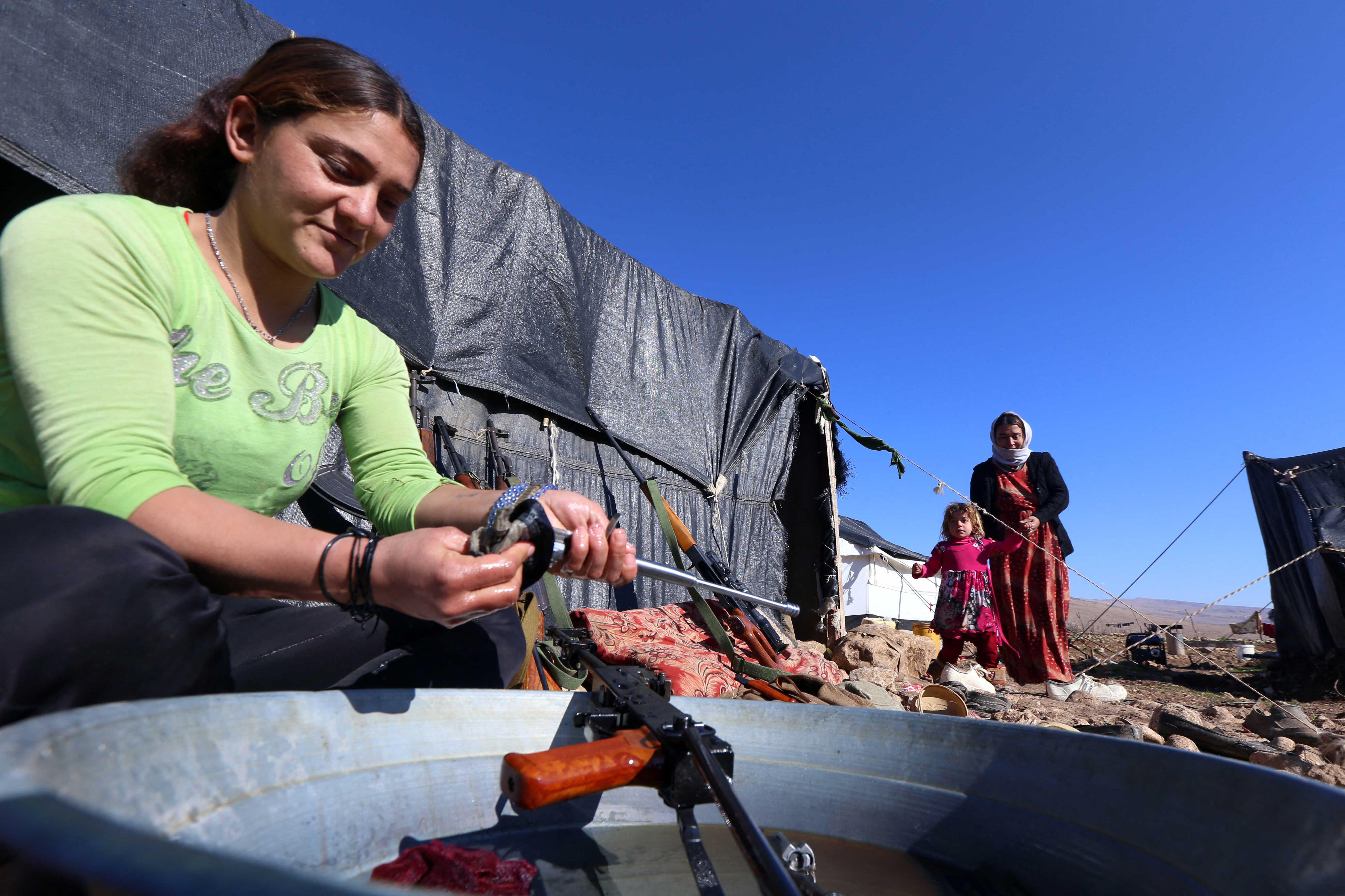 امرأة تنظف سلاحا منزليا في العراق.. حيث تنتشر الأسلحة بكثاقة
