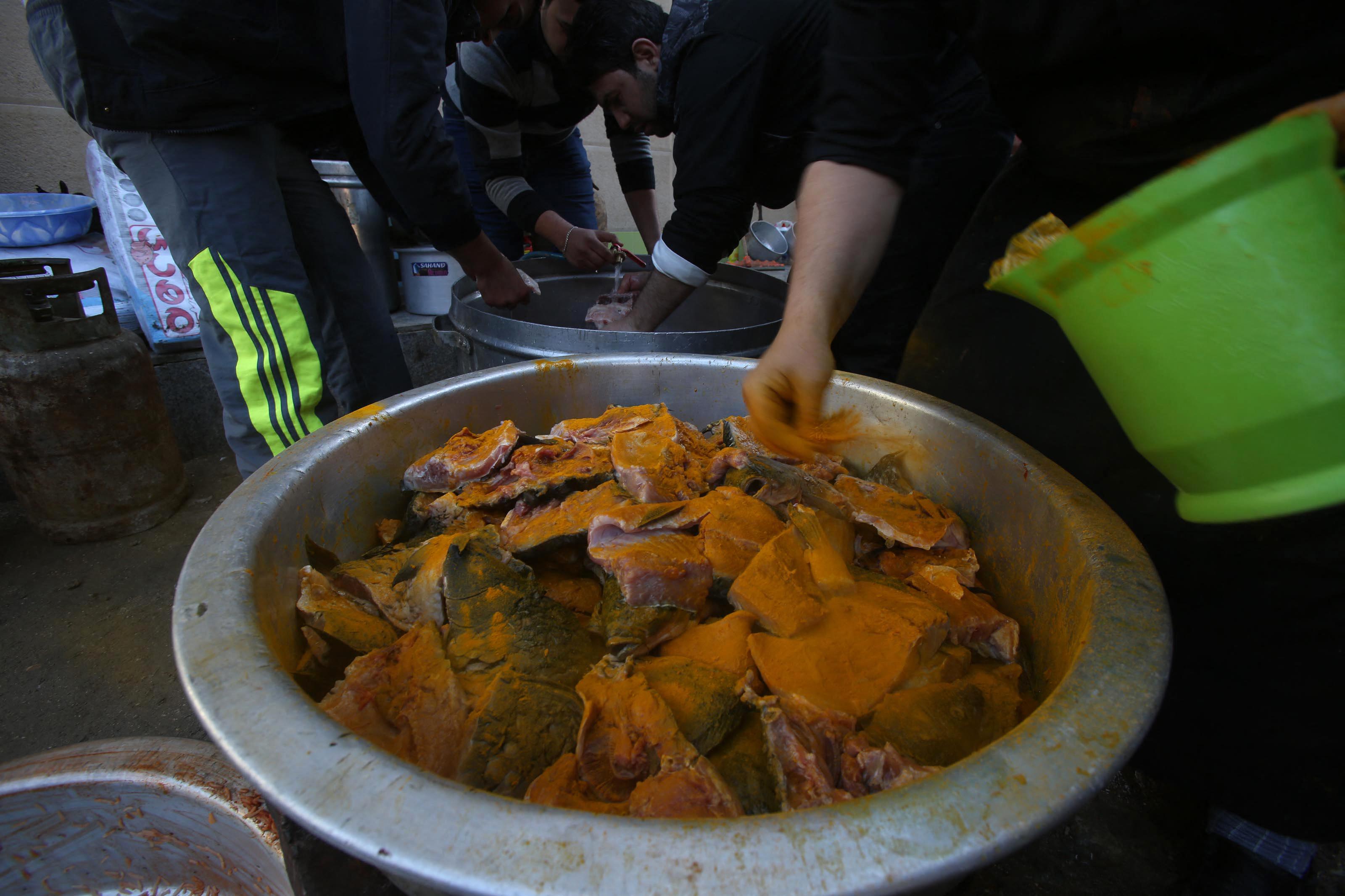 عراقية تتبل كميات من السمك استعدادا لقليه وتقديمه للزائرين