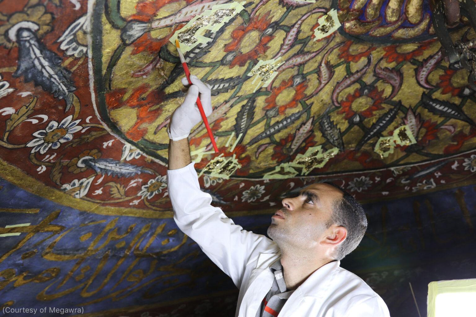 رئيس فريق الترميم مختار عبد العزيز يعمل على طلاء الخشب داخل ضريح الإمام محمد الشافعي في القاهرة