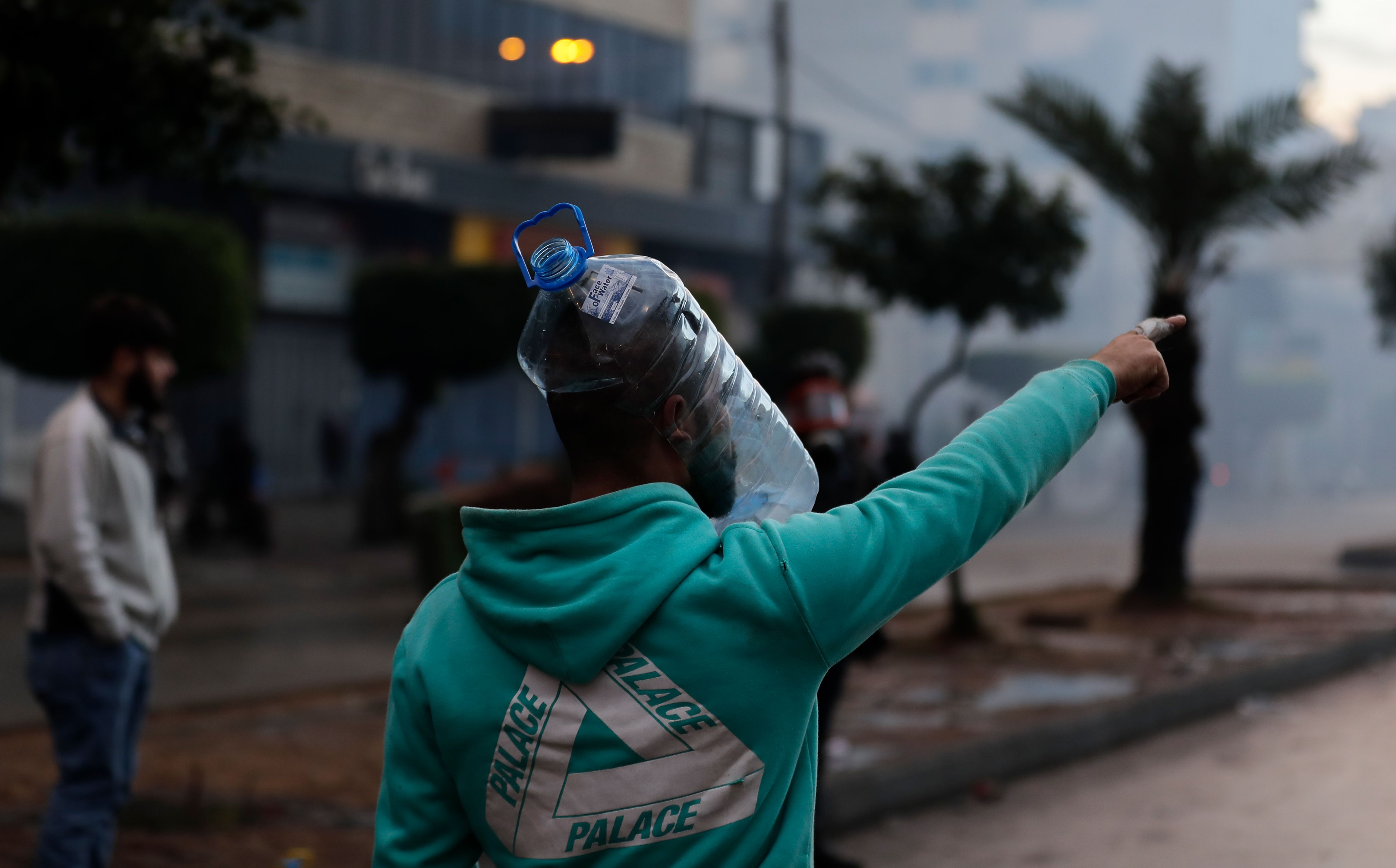 TOPSHOT - A Lebanese anti-government protester wearing a water bottle as a shield points during clashes with security forces in…